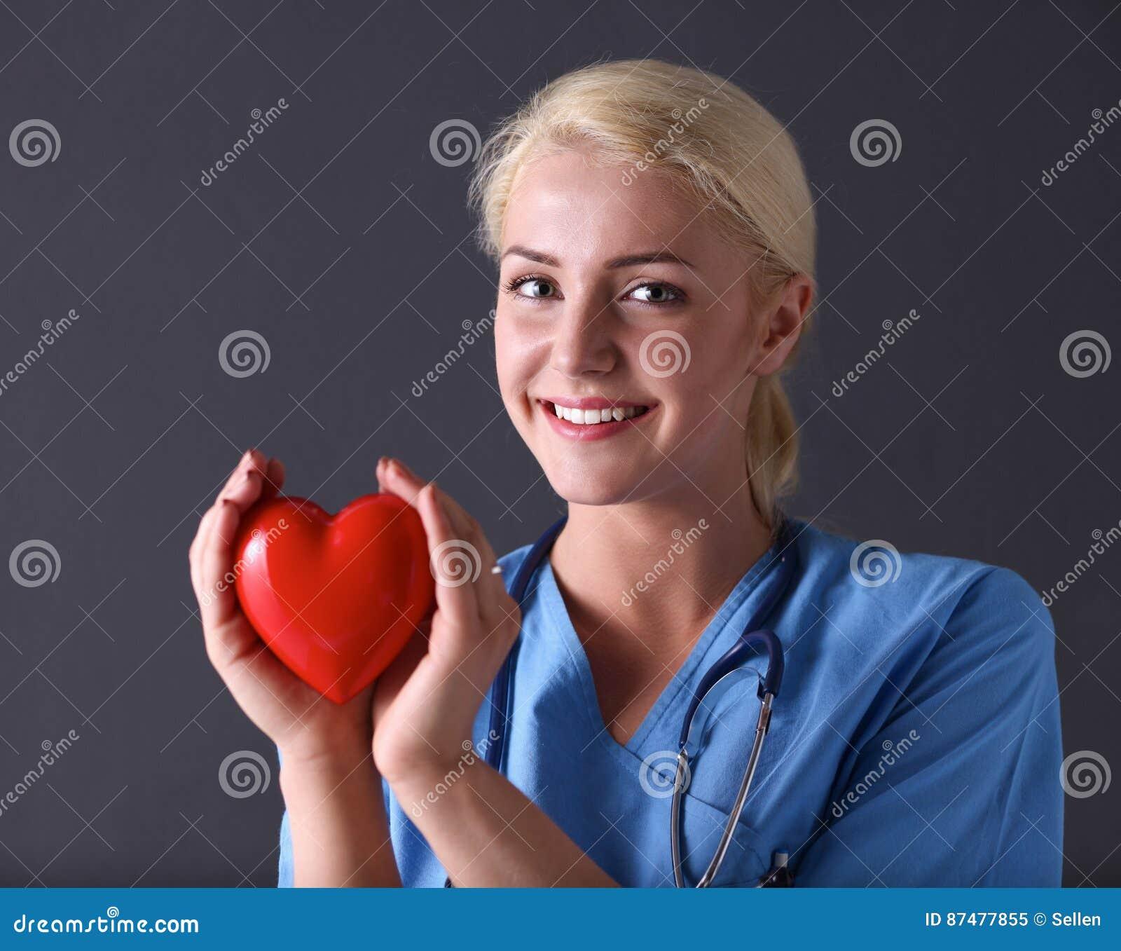 Доктор при стетоскоп держа сердце, на серой предпосылке