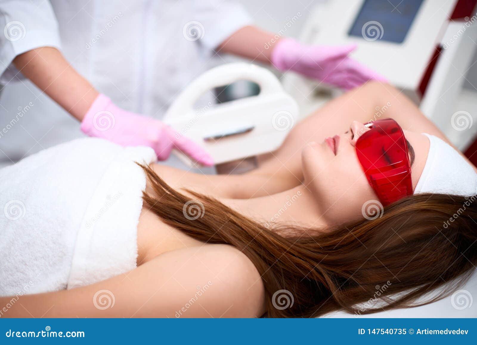 Доктор Beautician делая депиляцию удаления волос elos на милых подмышках молодой женщины в beuty салоне Оборудование астетическое