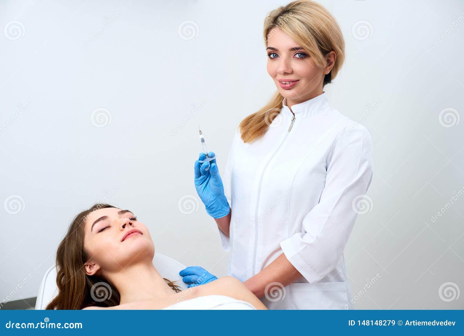 Доктор Cosmetologist стоя около пациента и держа перчатки перед деятельностью, впрыски botulinum шприца нося