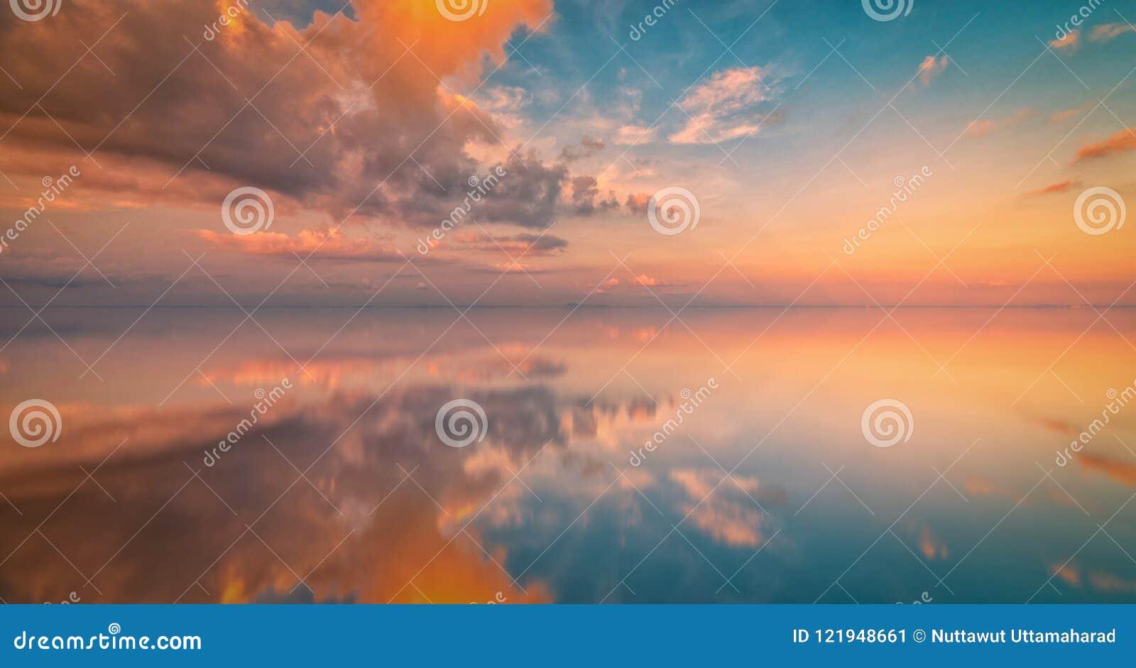 Долгая выдержка красочного неба и отражения захода солнца на море Vint