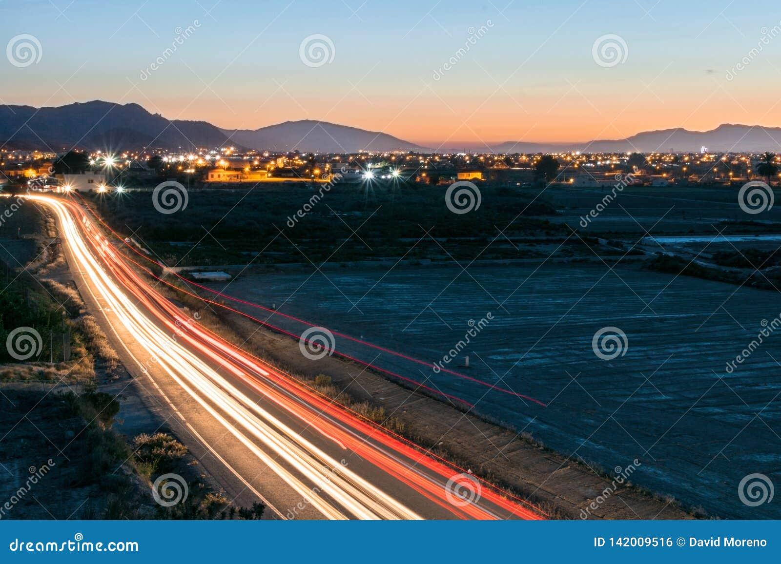 Долгая выдержка светлых следов автомобилей на дороге сельской местности