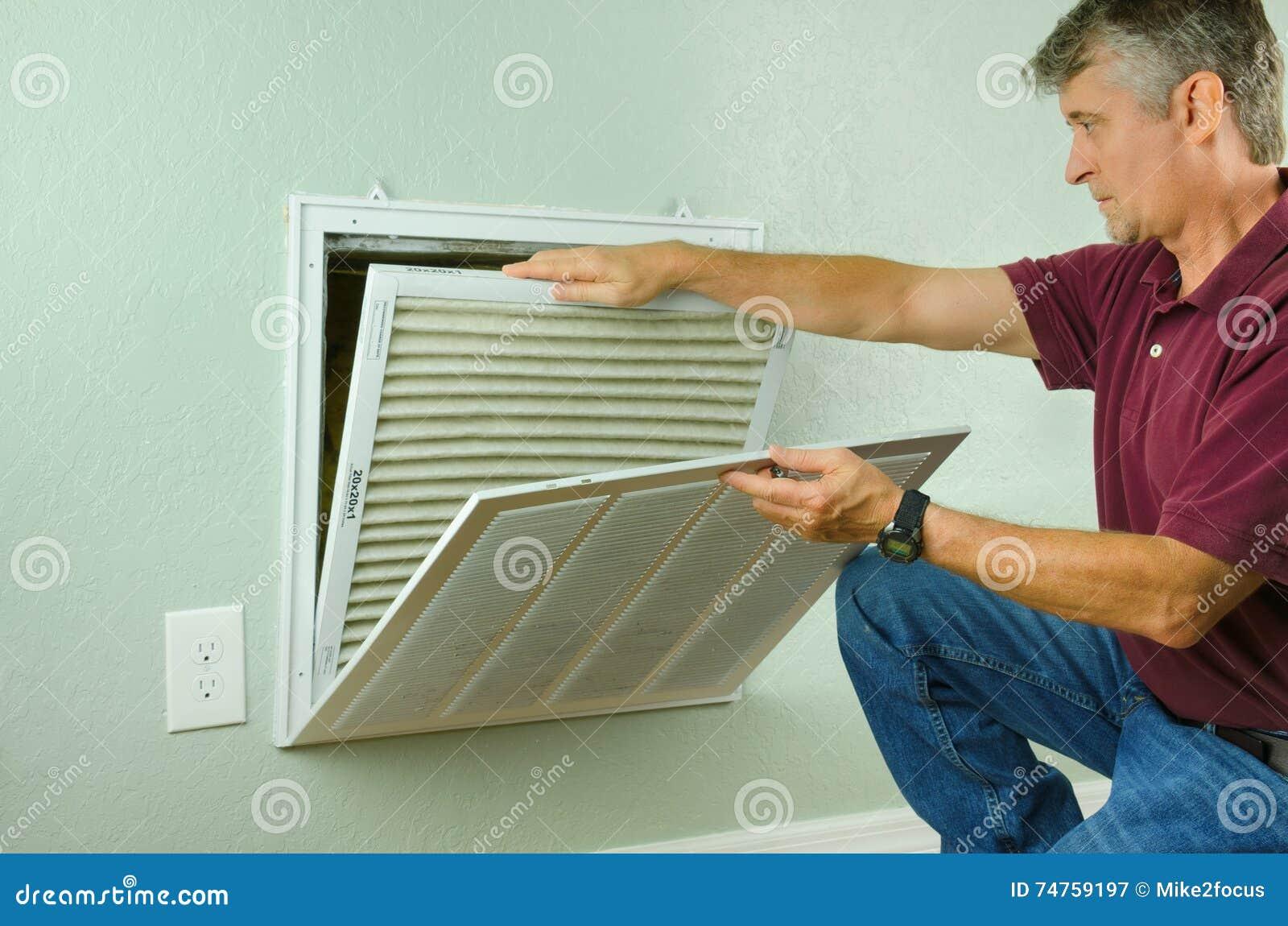 Домовладелец заменяя воздушный фильтр на кондиционере воздуха