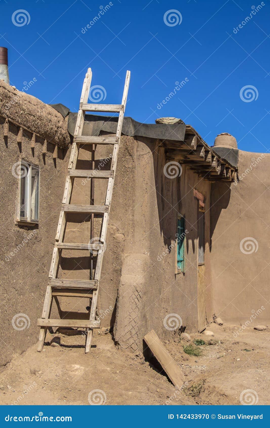 Домодельная деревянная лестница против стороны дома Пуэбло самана грязи куда бумага смолки кладется на крышу - с драматическими т