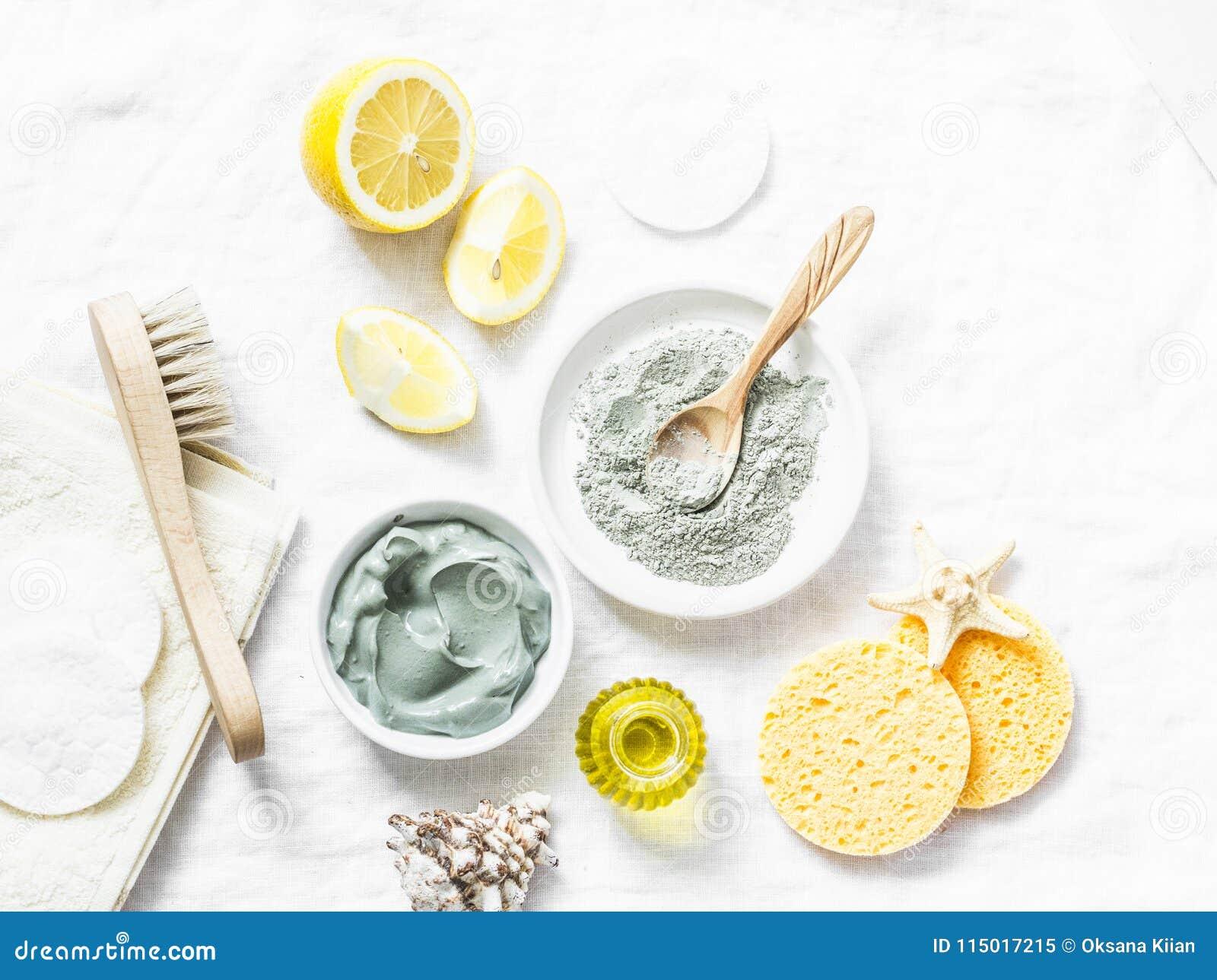 Домодельная маска ухода за лицом красоты Глина, лимон, масло, лицевая щетка - ингридиенты продуктов красоты на светлой предпосылк