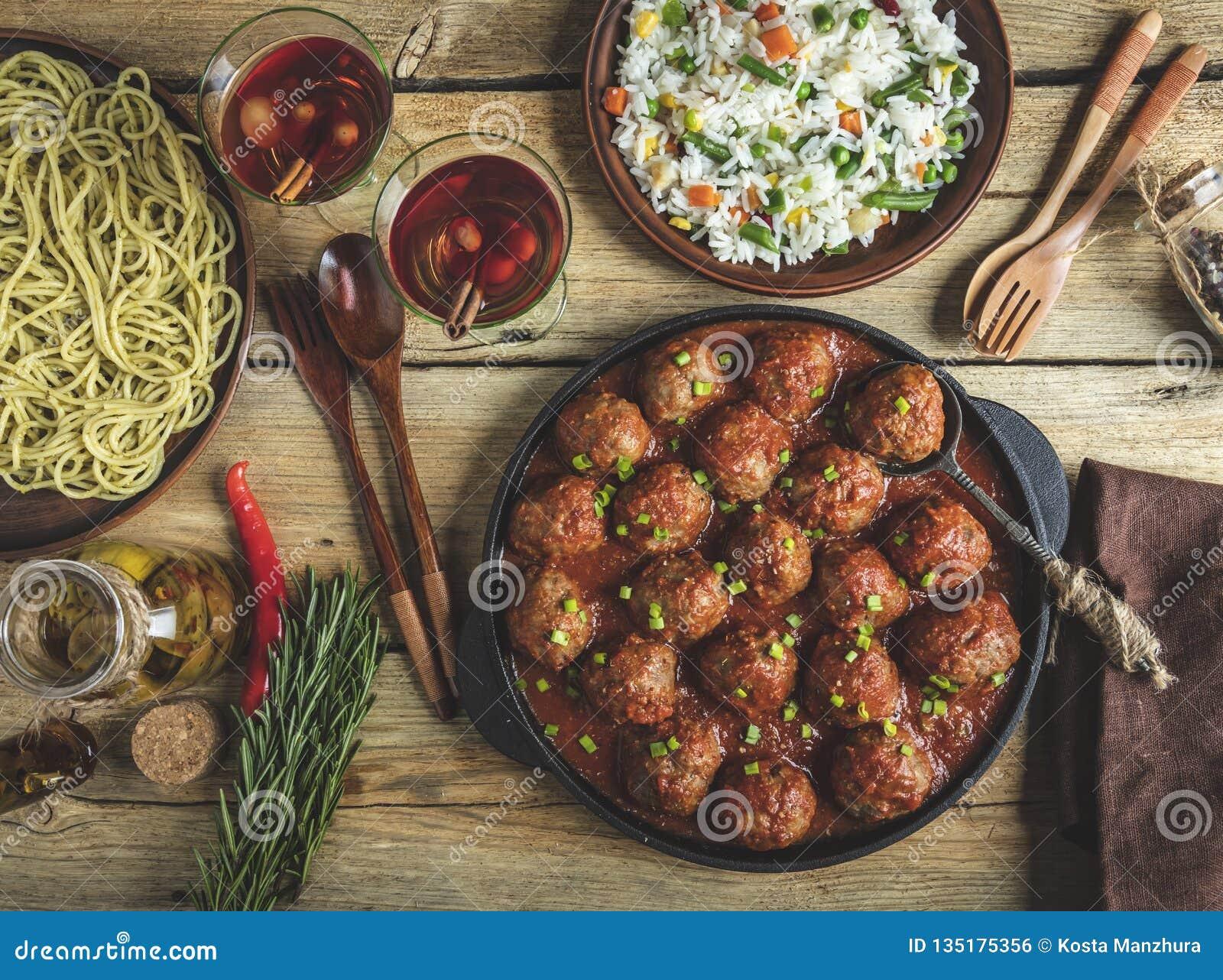 Домодельные фрикадельки в томатном соусе Сковорода на деревянной поверхности, рис с овощами, макаронные изделия