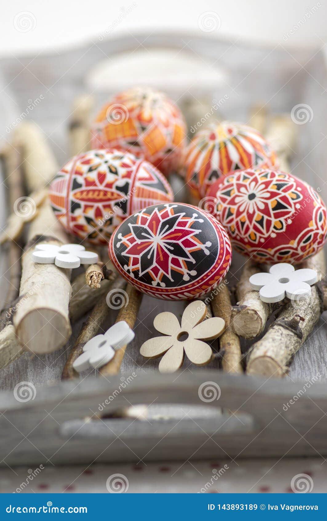 Домодельные handmade покрашенные пасхальные яйца на ветвях березы на сером деревянном подносе, традиционные яйца hnadcraft, белые