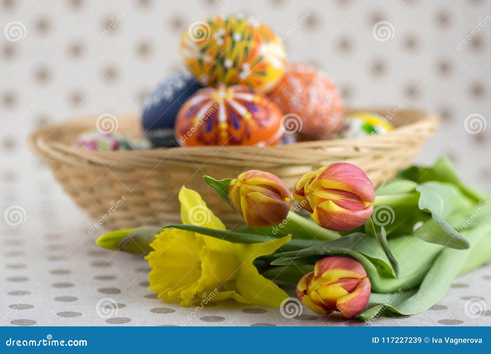 Домодельные handmade покрашенные пасхальные яйца на плетеной корзине, традиционной handcraft яичка