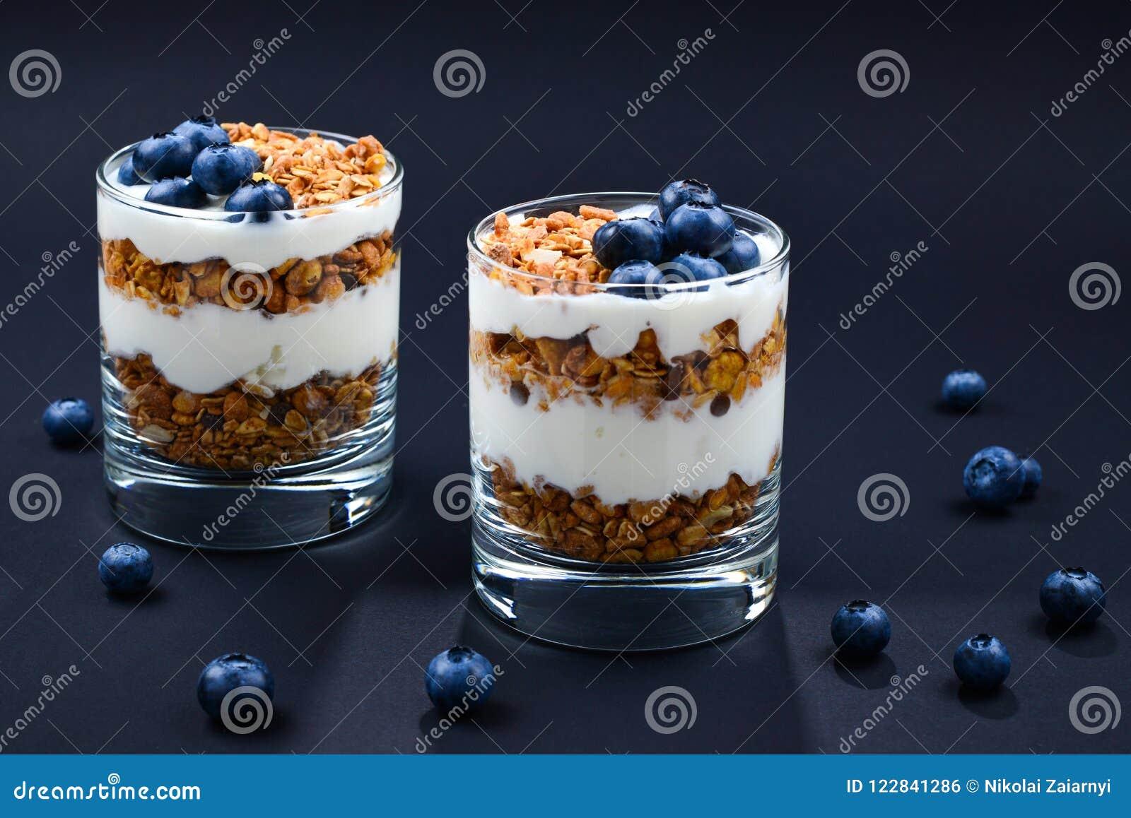 Домодельный испеченный granola с югуртом и голубиками в стекле дальше