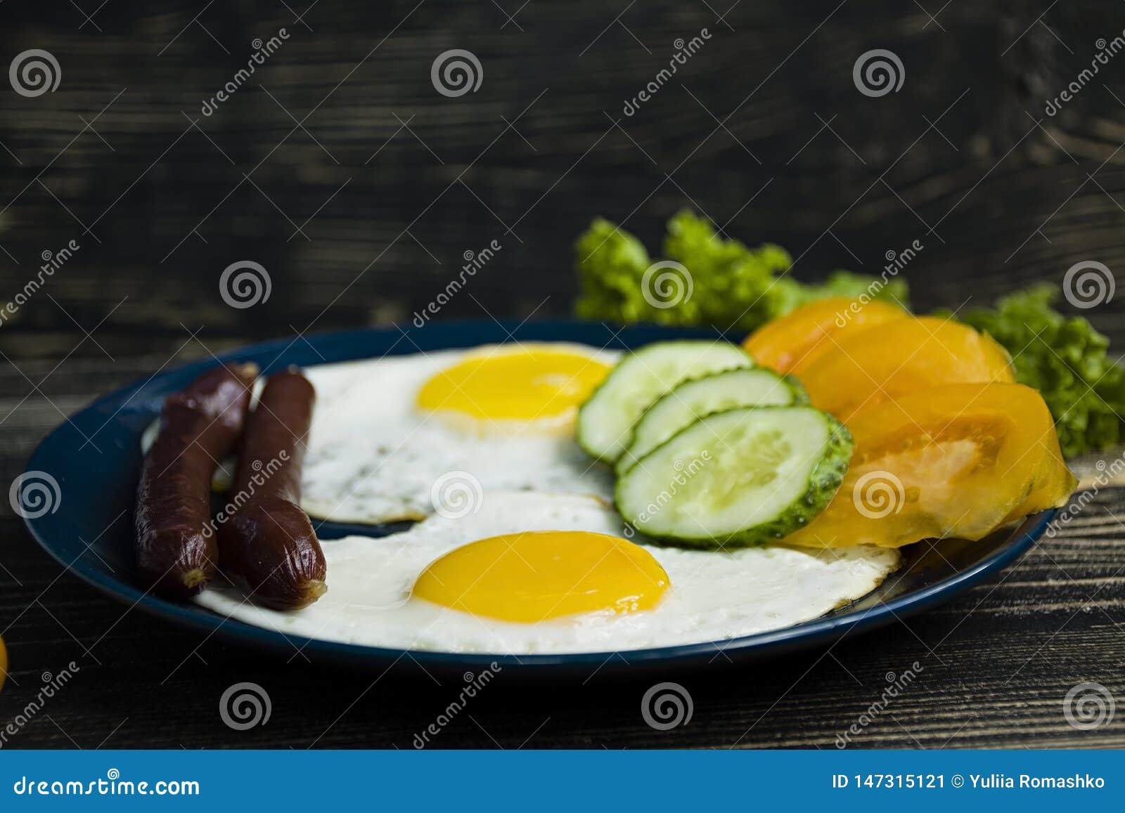 Домодельный очень вкусный завтрак с солнечной стороной вверх по яичнице, сосиске, томатам во взгляде сверху