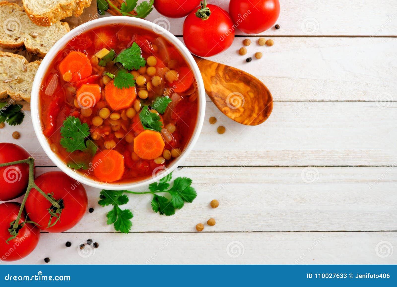 Домодельный томат, суп чечевицы, выше, угловая граница на белой древесине