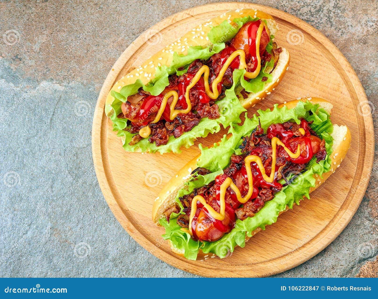 2 домодельных хот-дога с отбензиниваниями салата, бекона и лука