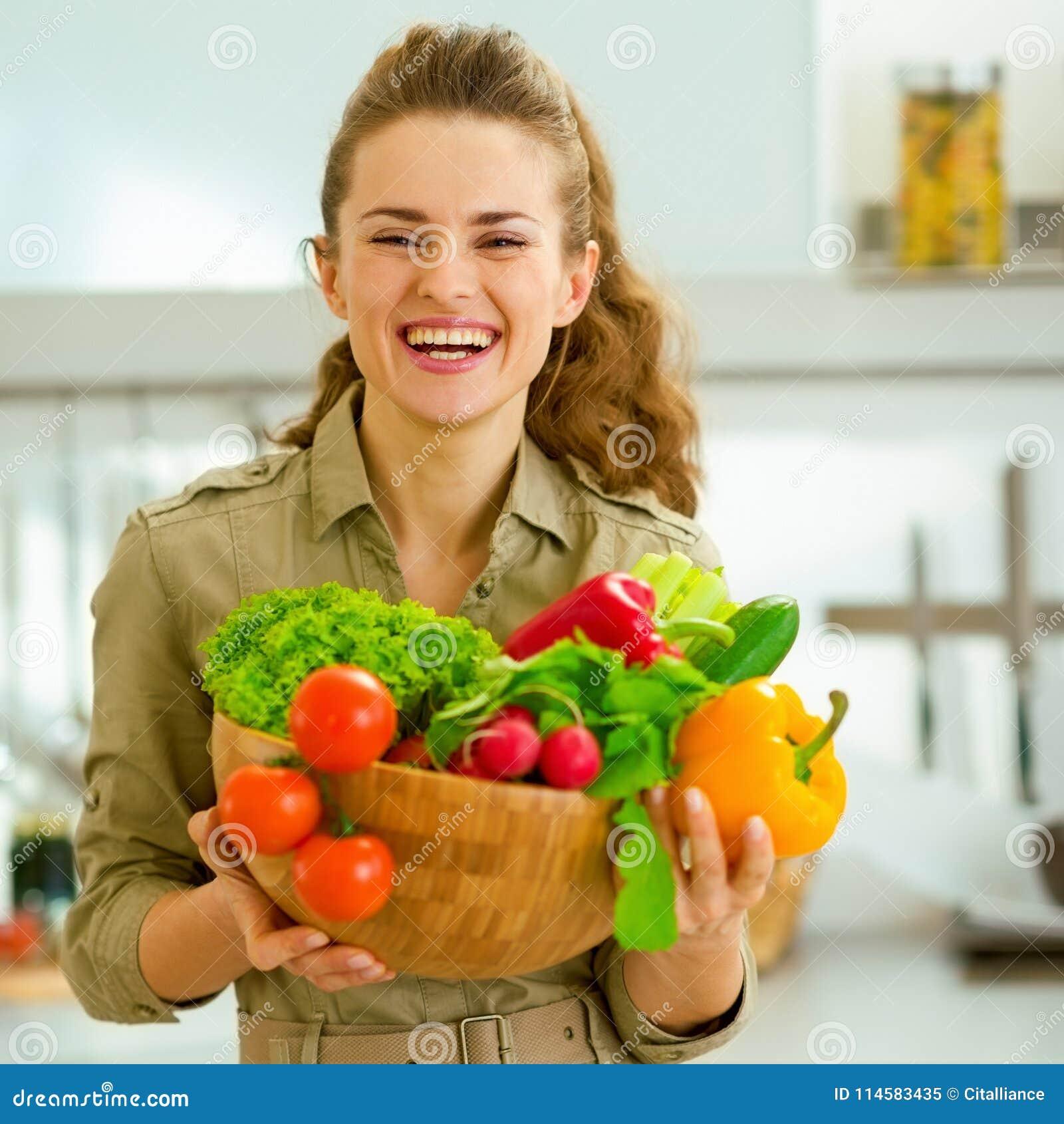 Домохозяйка держа плиту полный овощей в современном