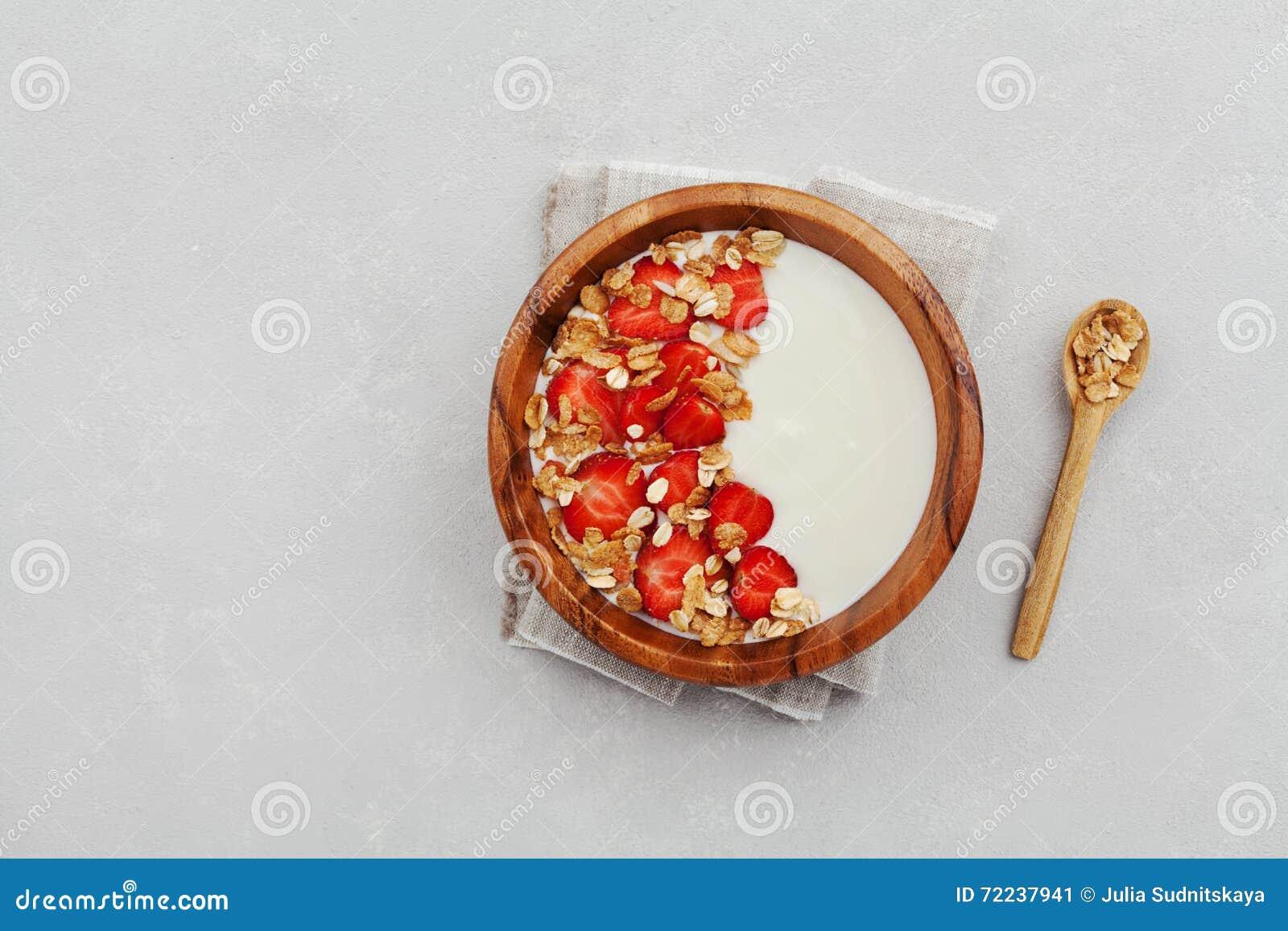 Домодельный югурт в деревянном шаре с клубникой и granola или muesli на светлой таблице, здоровом завтраке сверху