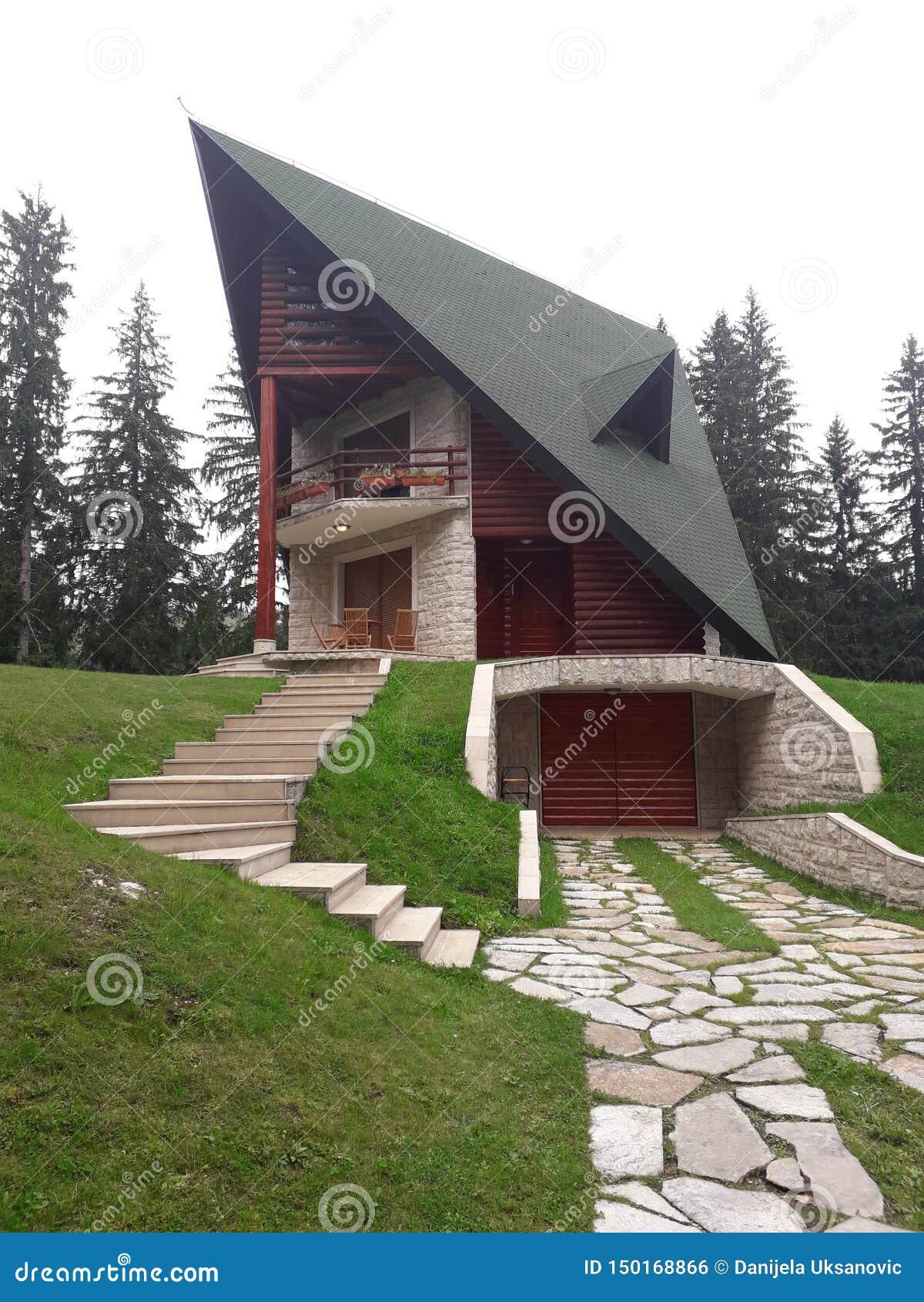 Дом горы красивый на холме расположен в лесе рядом с озером