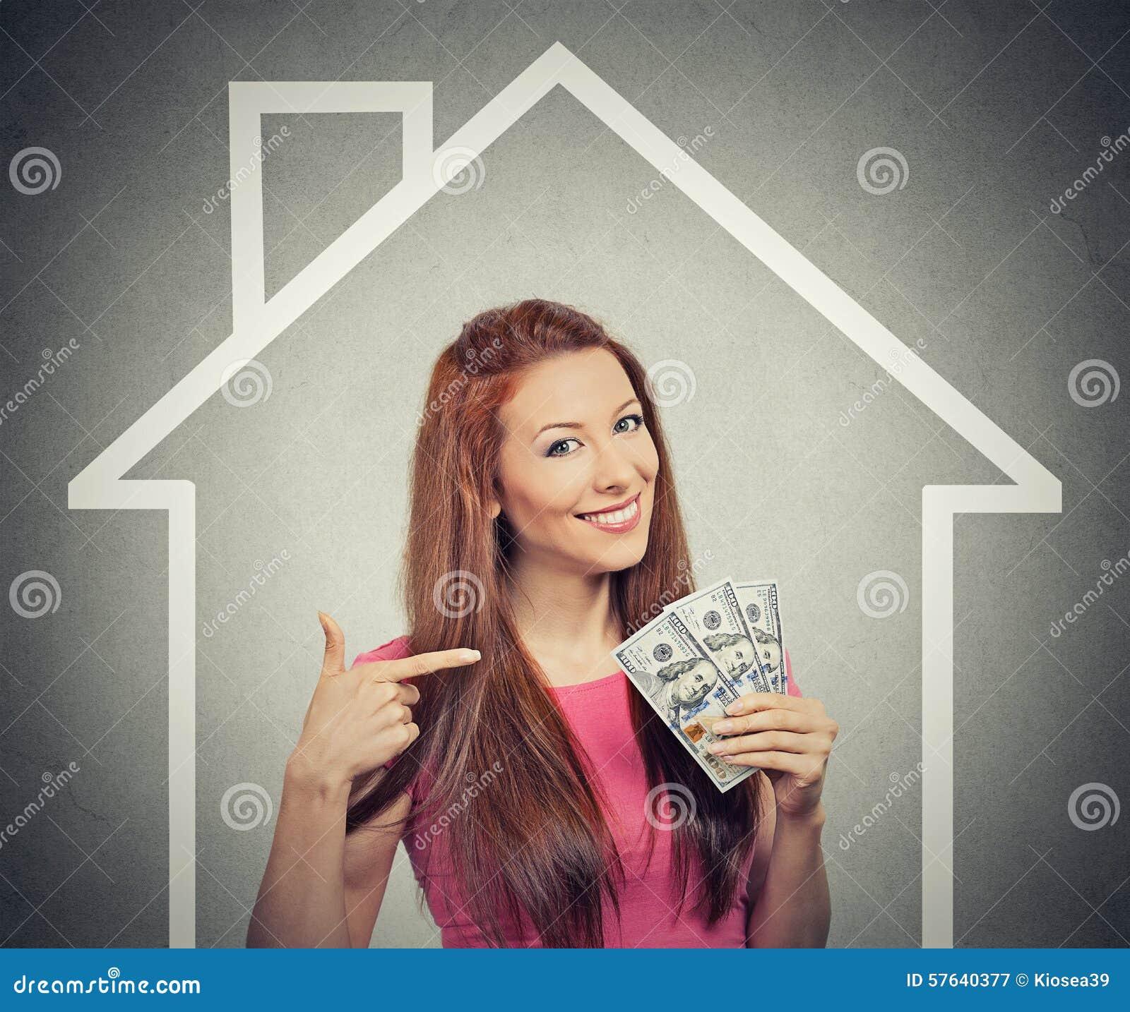Дом, деньги, концепция людей Успешная бизнес-леди держа деньги наличных денег доллара