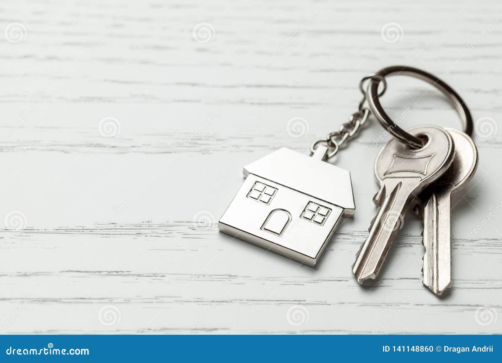 Дом и ключи Keychain на белой деревянной предпосылке Скопируйте космос для текста