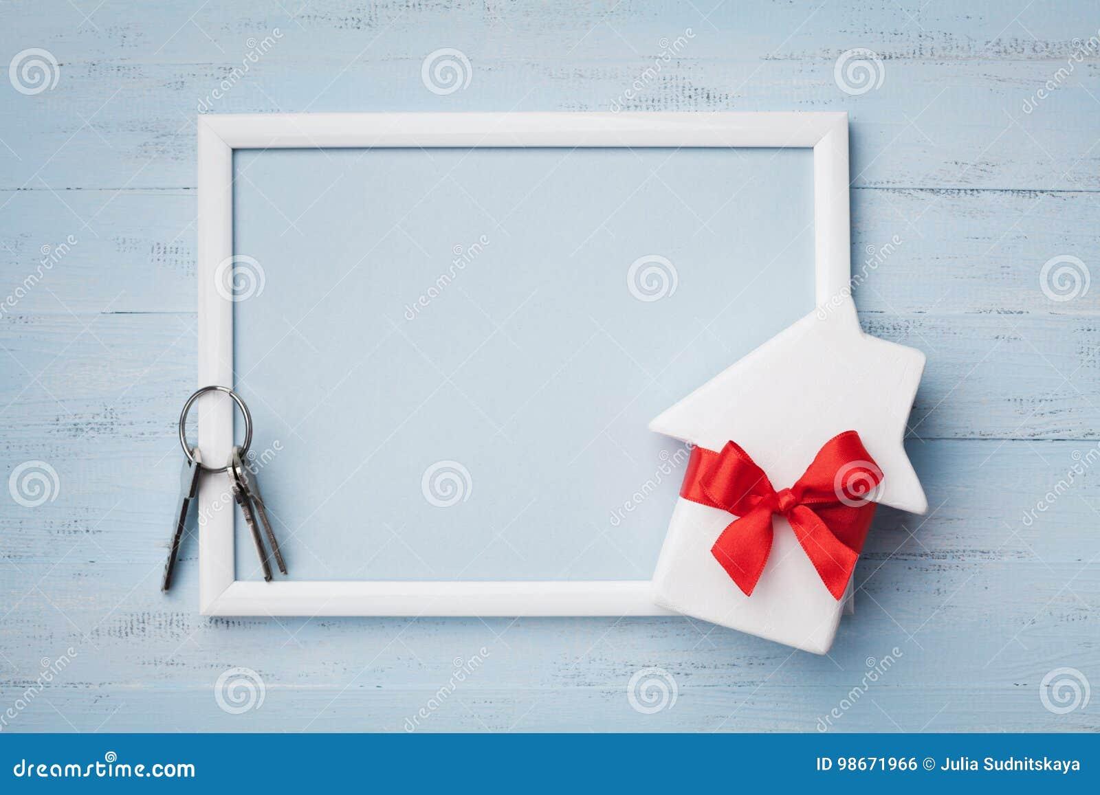 Дом с лентой, рамкой и keychain на деревянной предпосылке Покупать новый дом, планируя новоселье, подарок или продажу недвижимост