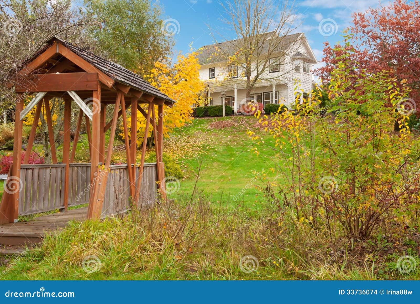 Дом фермы белой лошади американский во время падения с зеленой травой.