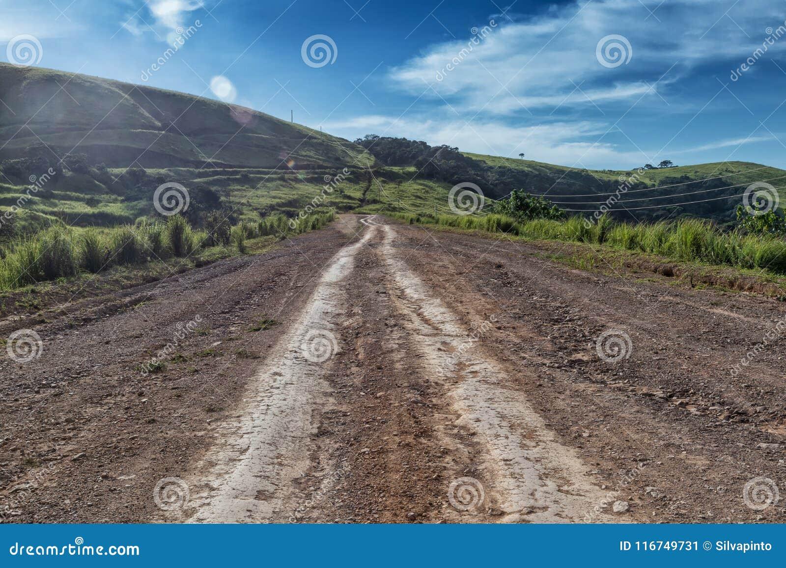 Дорога грязи с метками автошины бежит через зеленую долину в Malanje anisette вышесказанного