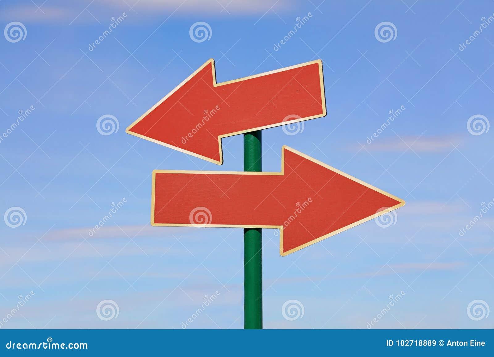 Дорожный знак с 2 красными стрелками над голубым небом