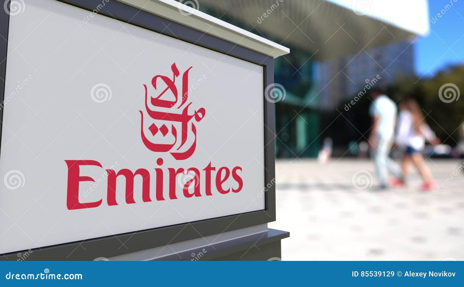 Доска signage улицы с логотипом авиакомпании эмиратов Запачканный центр офиса и идя предпосылка людей Редакционное 3D