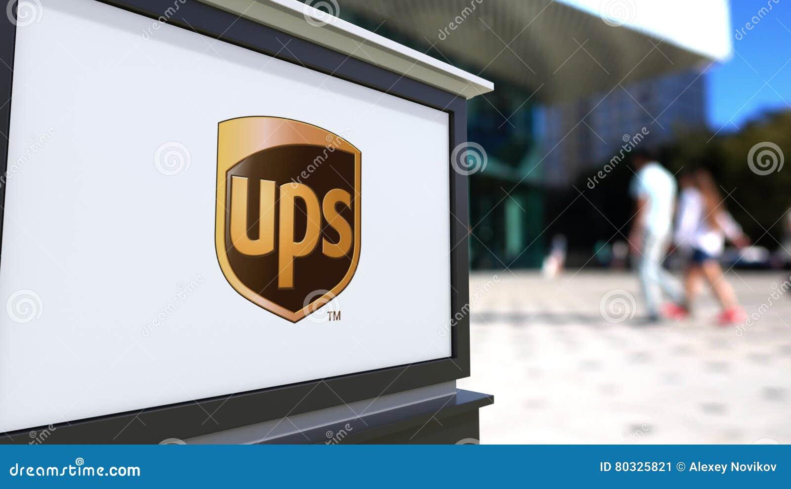 Доска signage улицы с логотипом UPS United Parcel Service Запачканный центр офиса и идя предпосылка людей редакционо