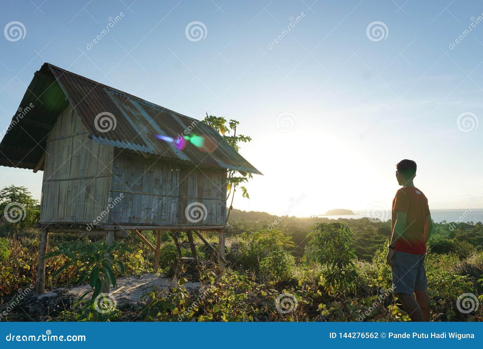 Достигаемость молодого человека к верхней части холма после этого наслаждается восходом солнца от верхней части