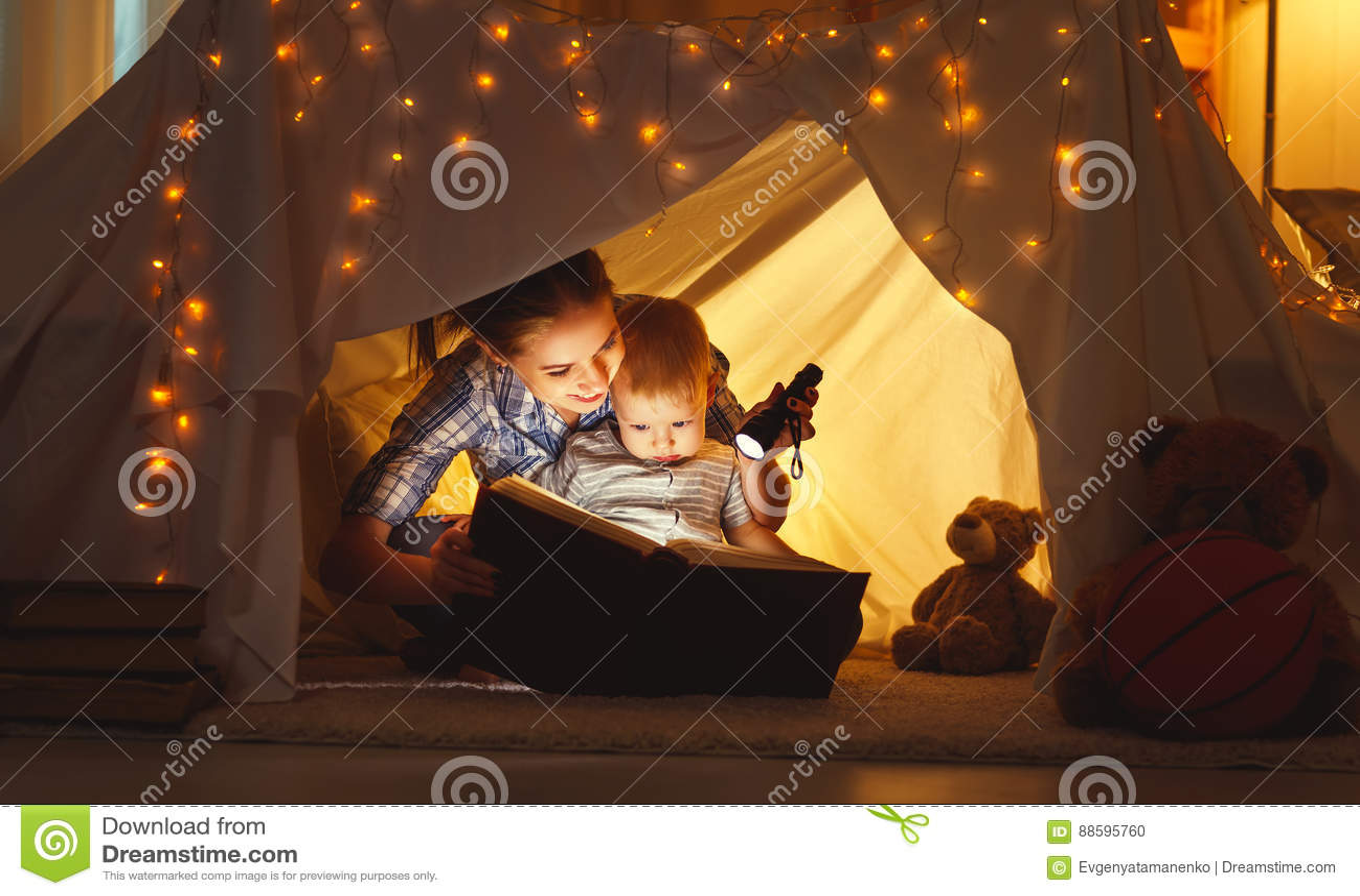 Дочь матери и ребенка с книгой и электрофонарем перед идет