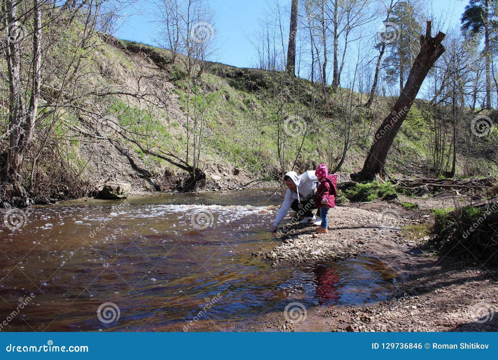 Дочь прогулки с его отцом в природе около реки
