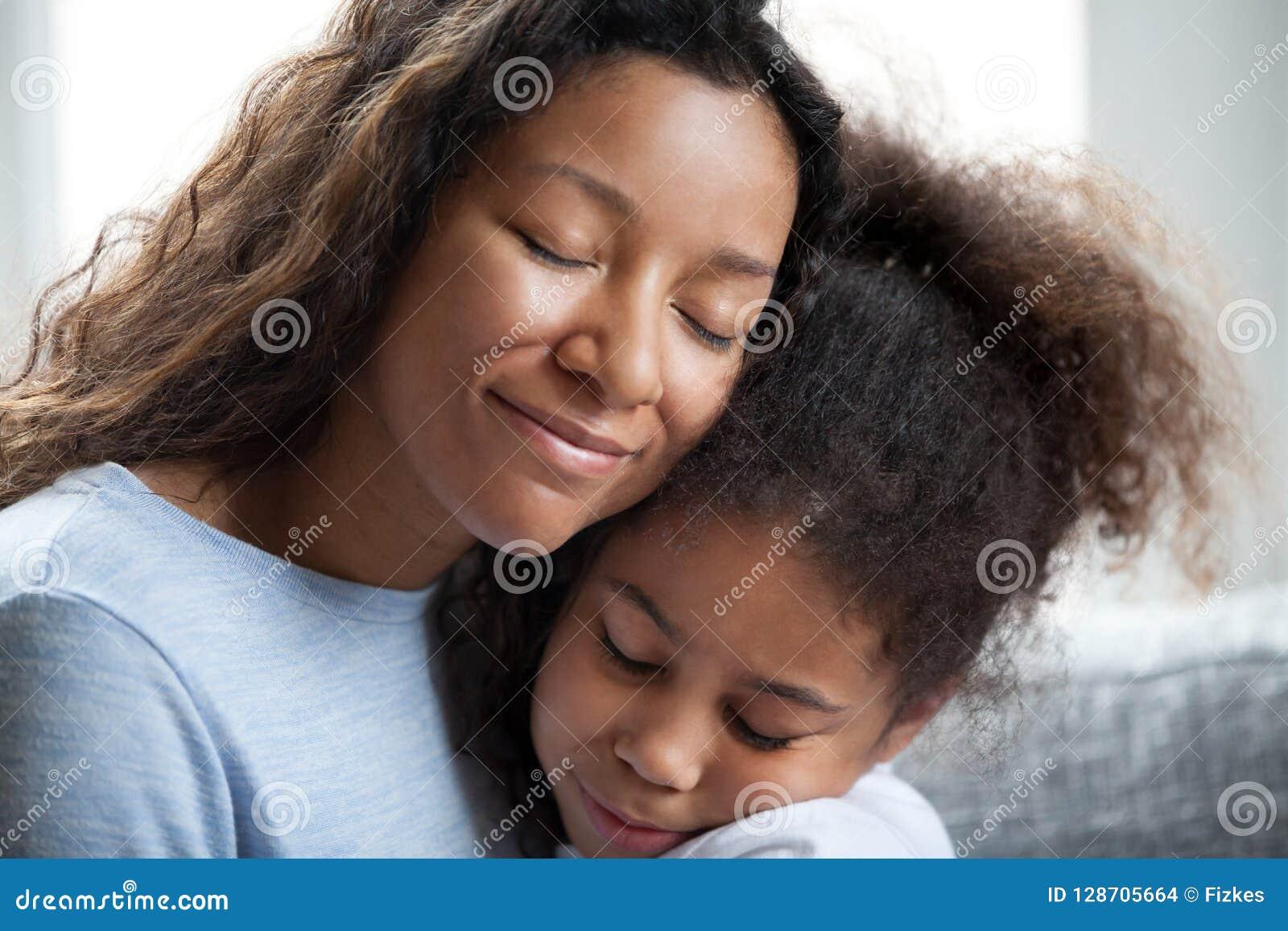 Дочь preschool любящего черного объятия матери маленькая