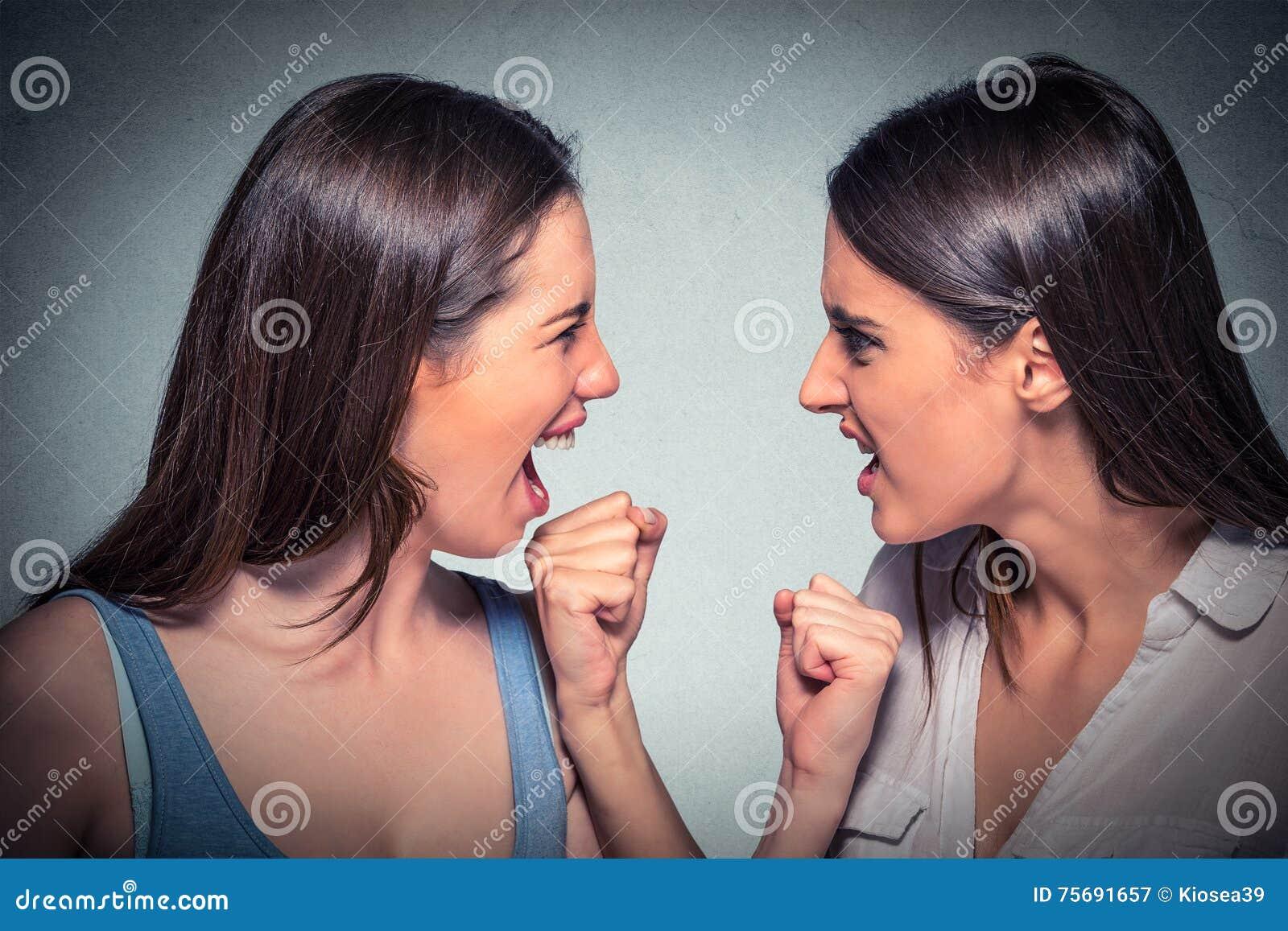Драка 2 женщин Сердитые девушки смотря один другого кричащий