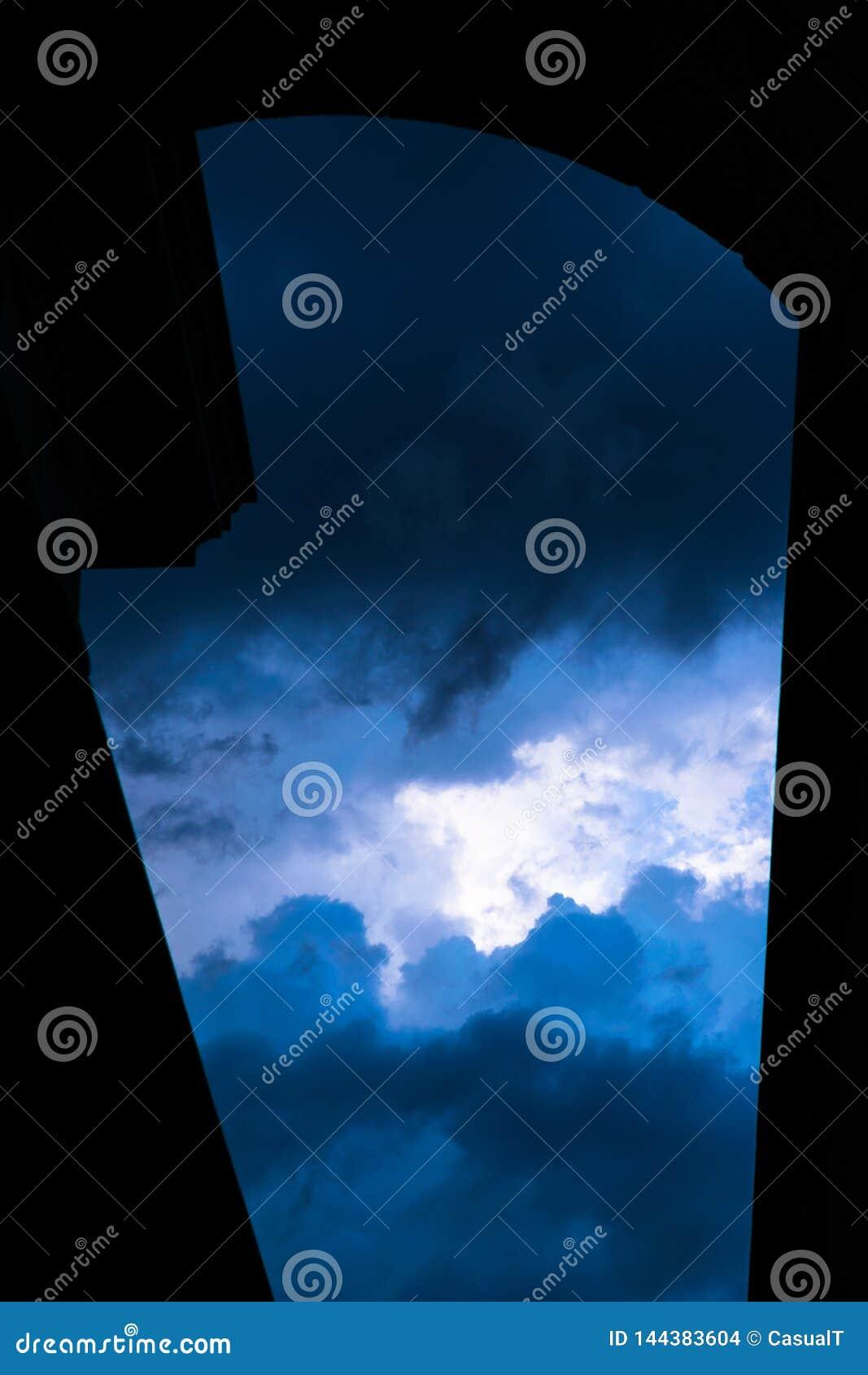 Драматическое, темное и наполненное облак небо обрамленное архитектурноакустическим силуэтом, Манхэттен, Нью-Йорк, NY