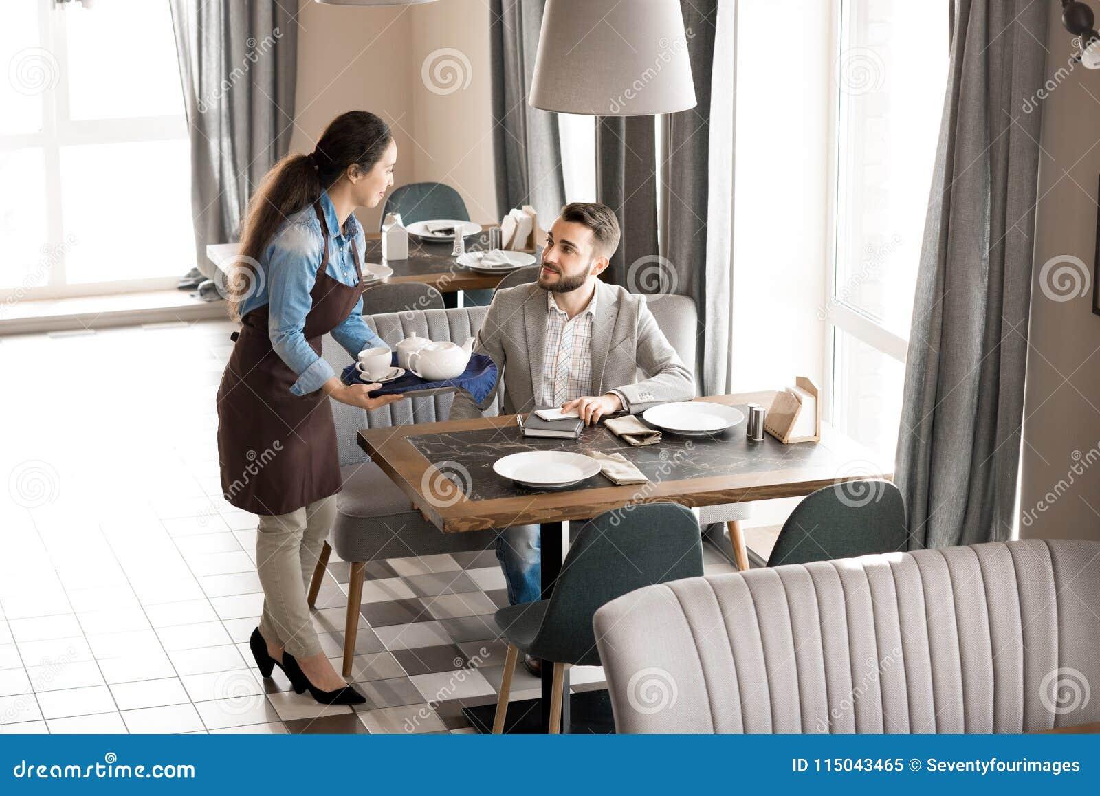 Дружелюбная официантка давая чай к клиенту