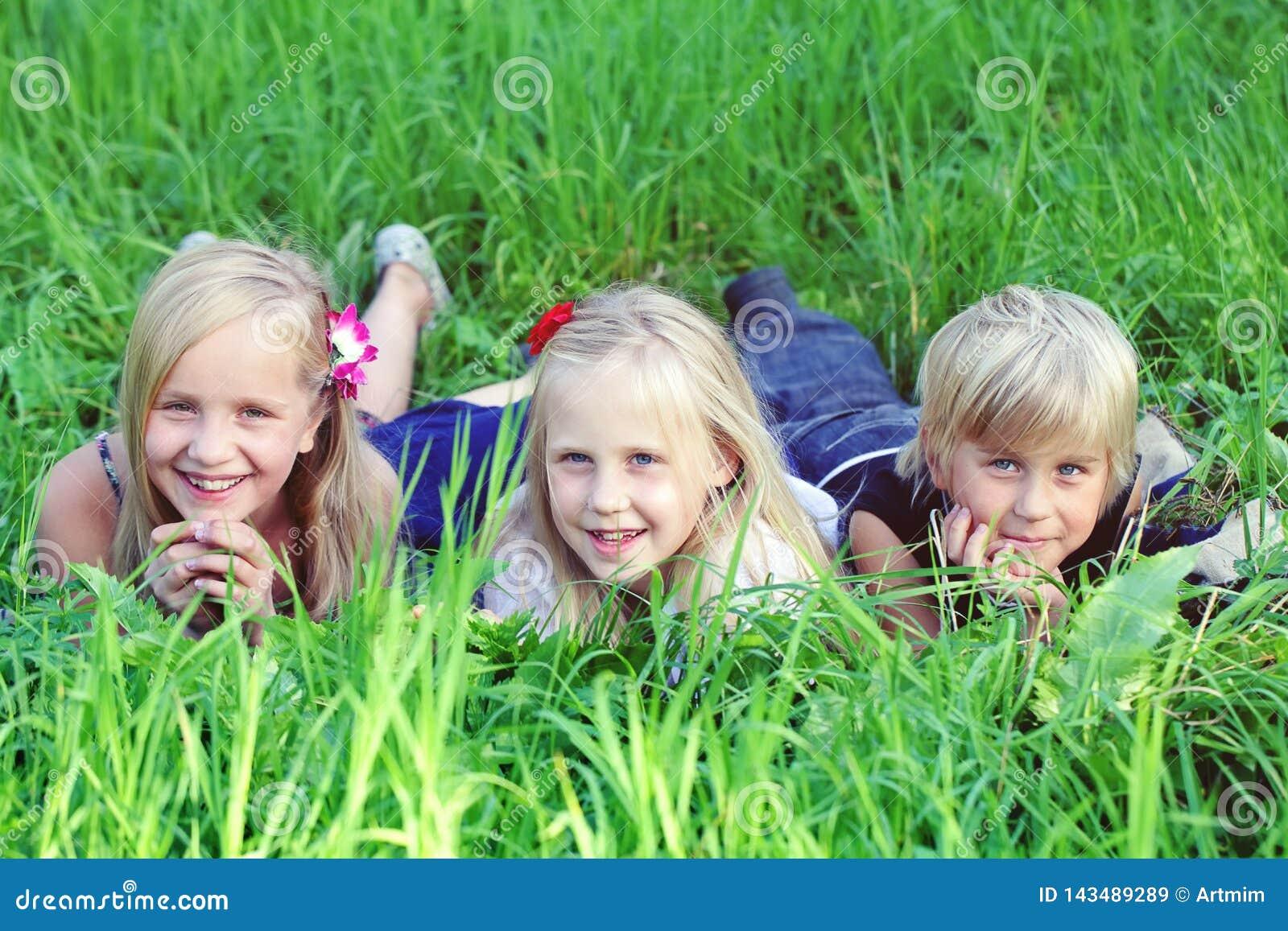 Дружелюбные дети лежа на зеленой траве в парке лета