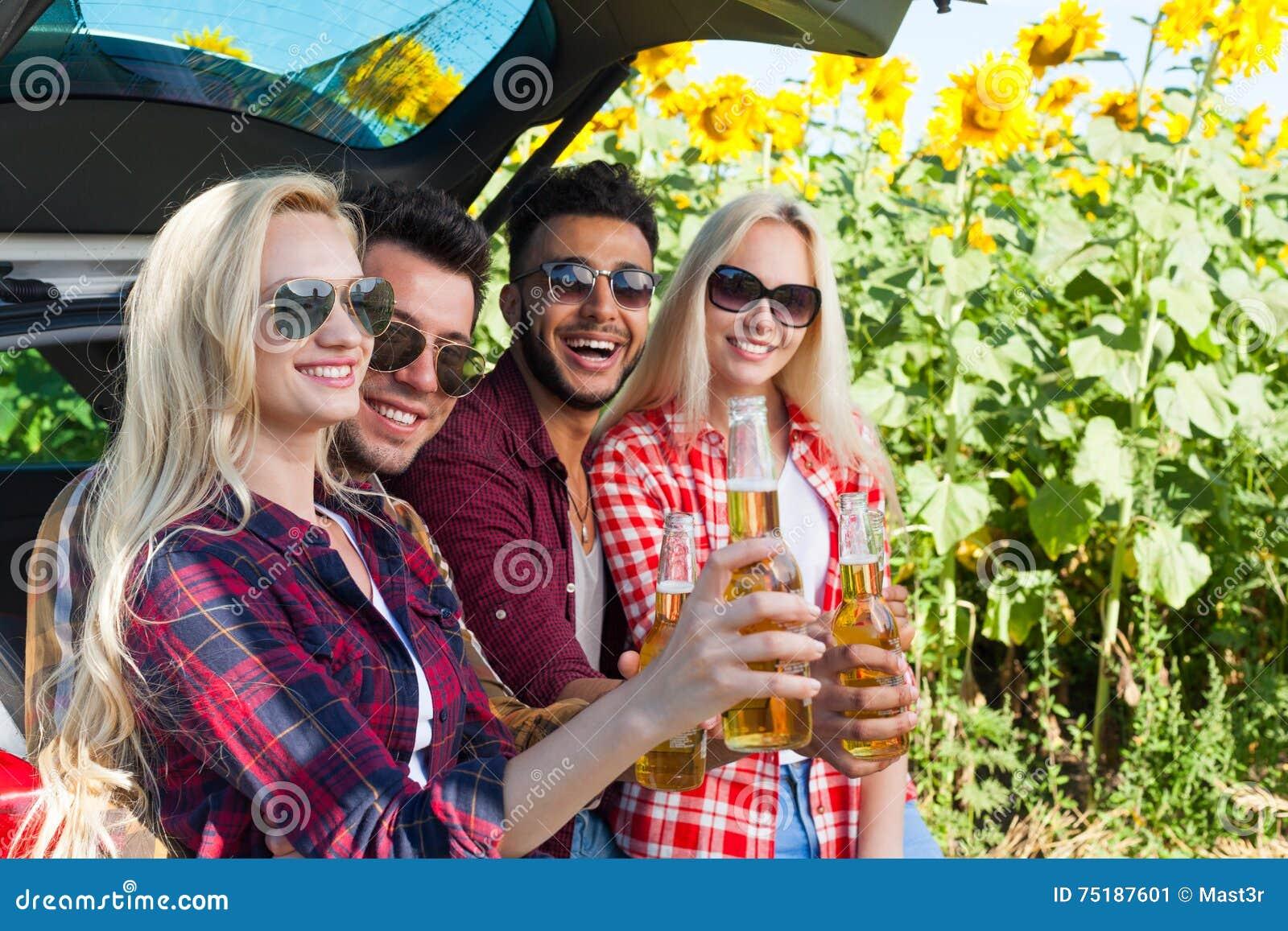 Друзья выпивая пиво провозглашать clink разливают сидеть по бутылкам в сельской местности багажника автомобиля внешней