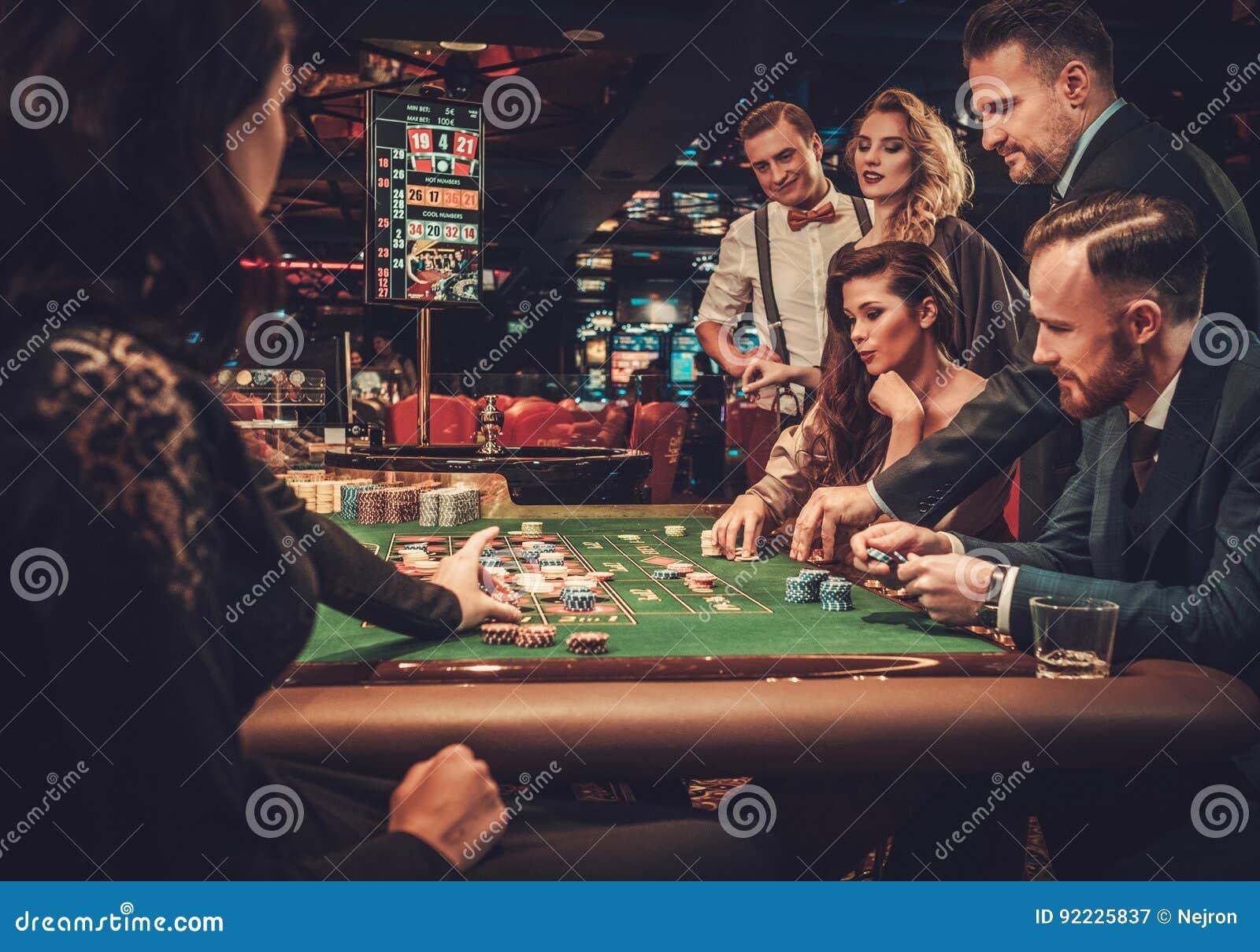 Друзья высшего класса играя в азартные игры в казино