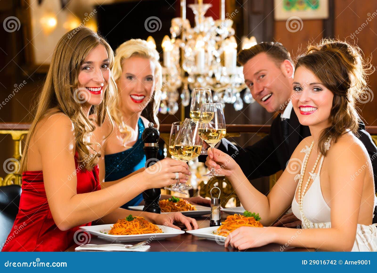 Друзья в стеклах очень хороших clink ресторана