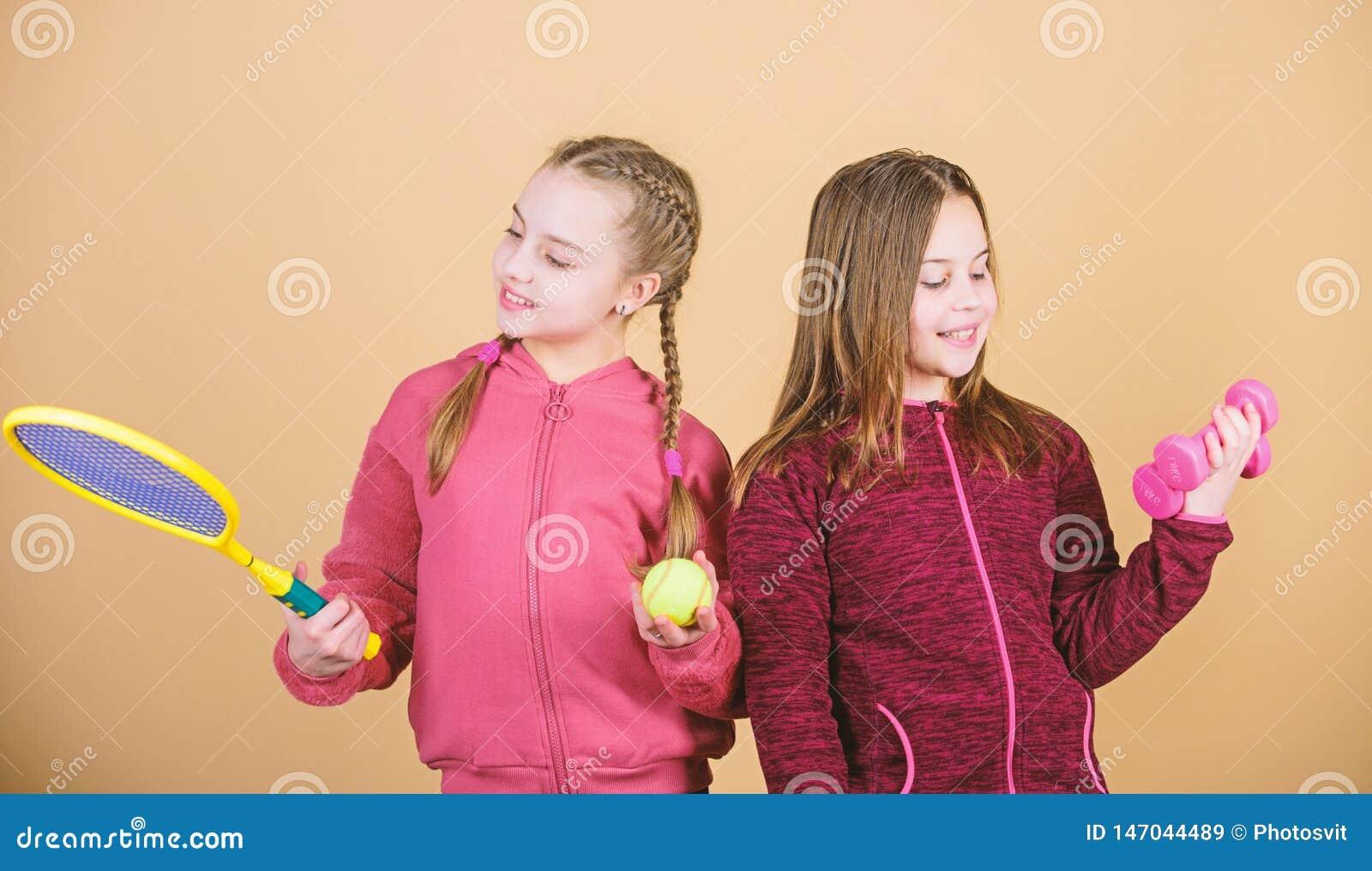 Друзья готовые для тренировки Пути помочь детям найти спорт они наслаждаются Дети девушек милые с гантелями оборудования спорта и