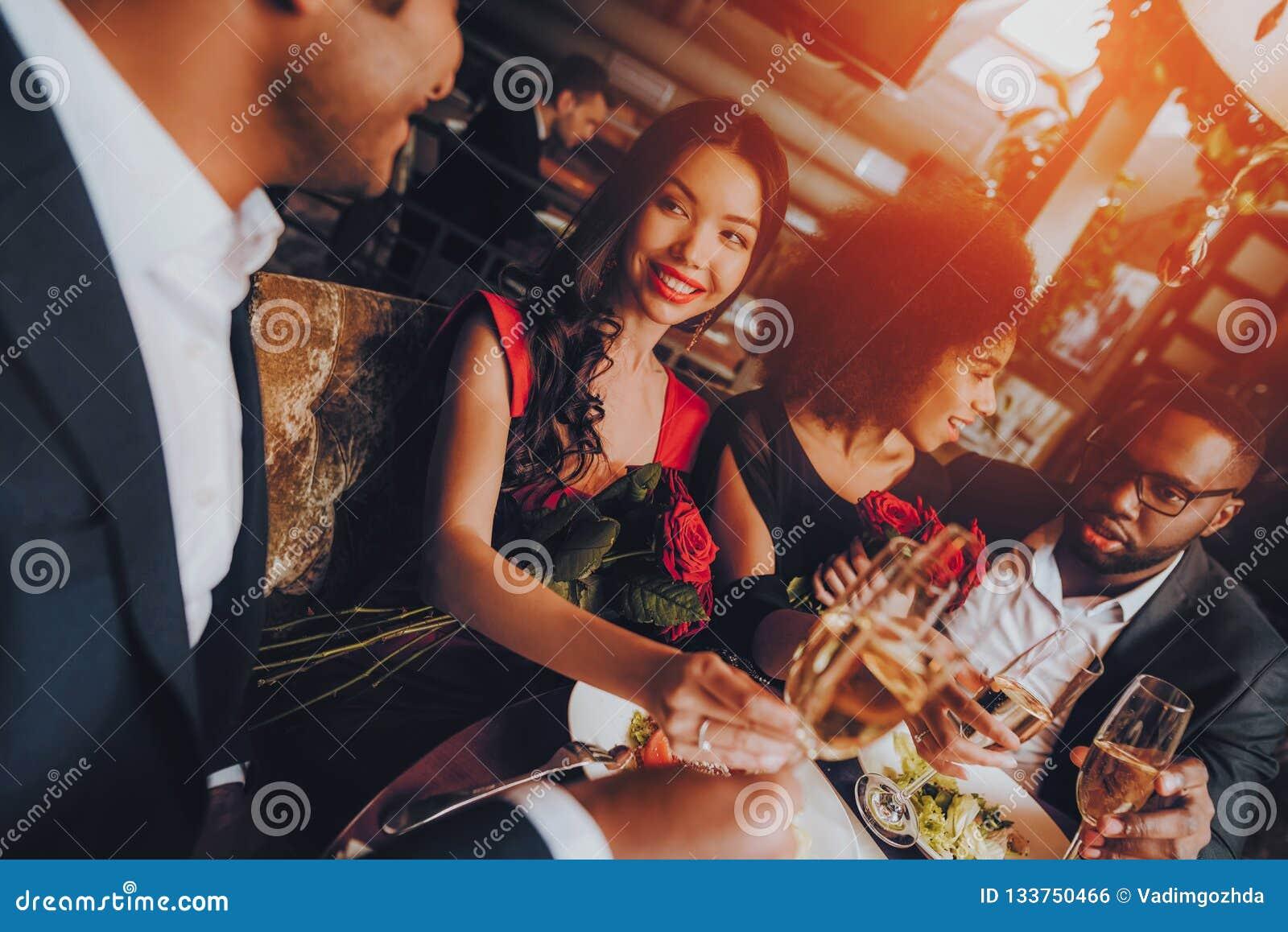 Друзья группы счастливые наслаждаясь датировать в ресторане