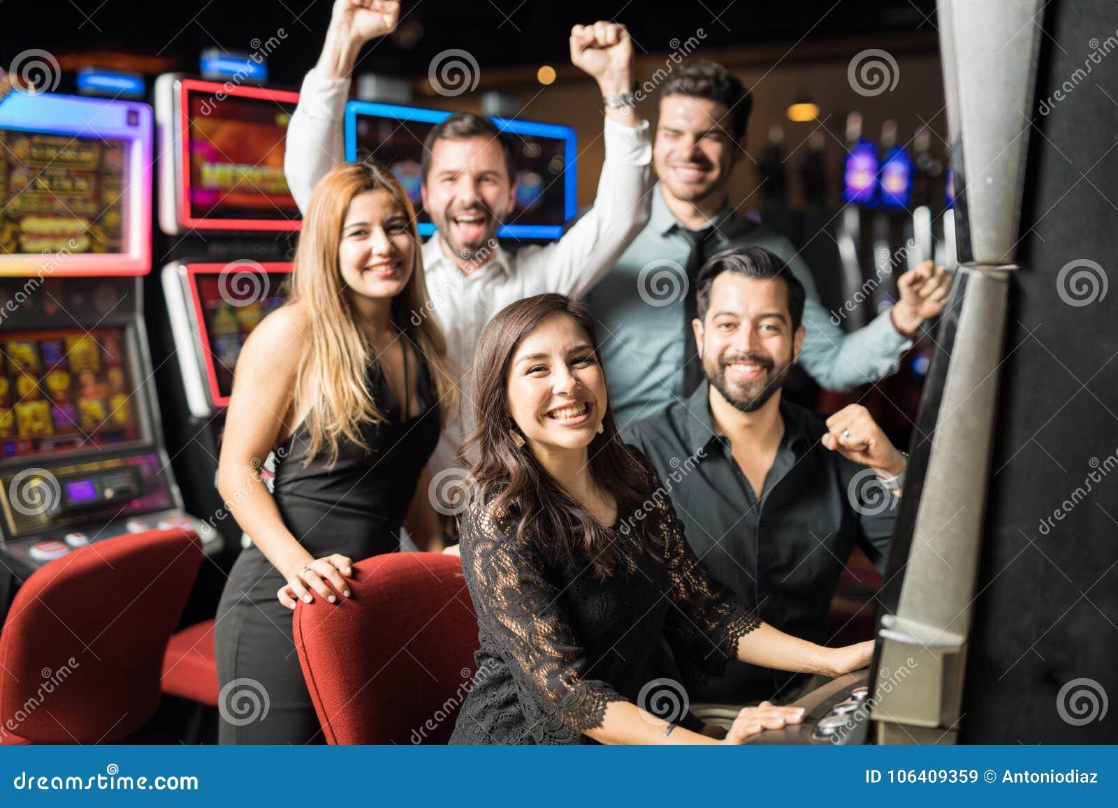 Друзья играя шлицы в казино