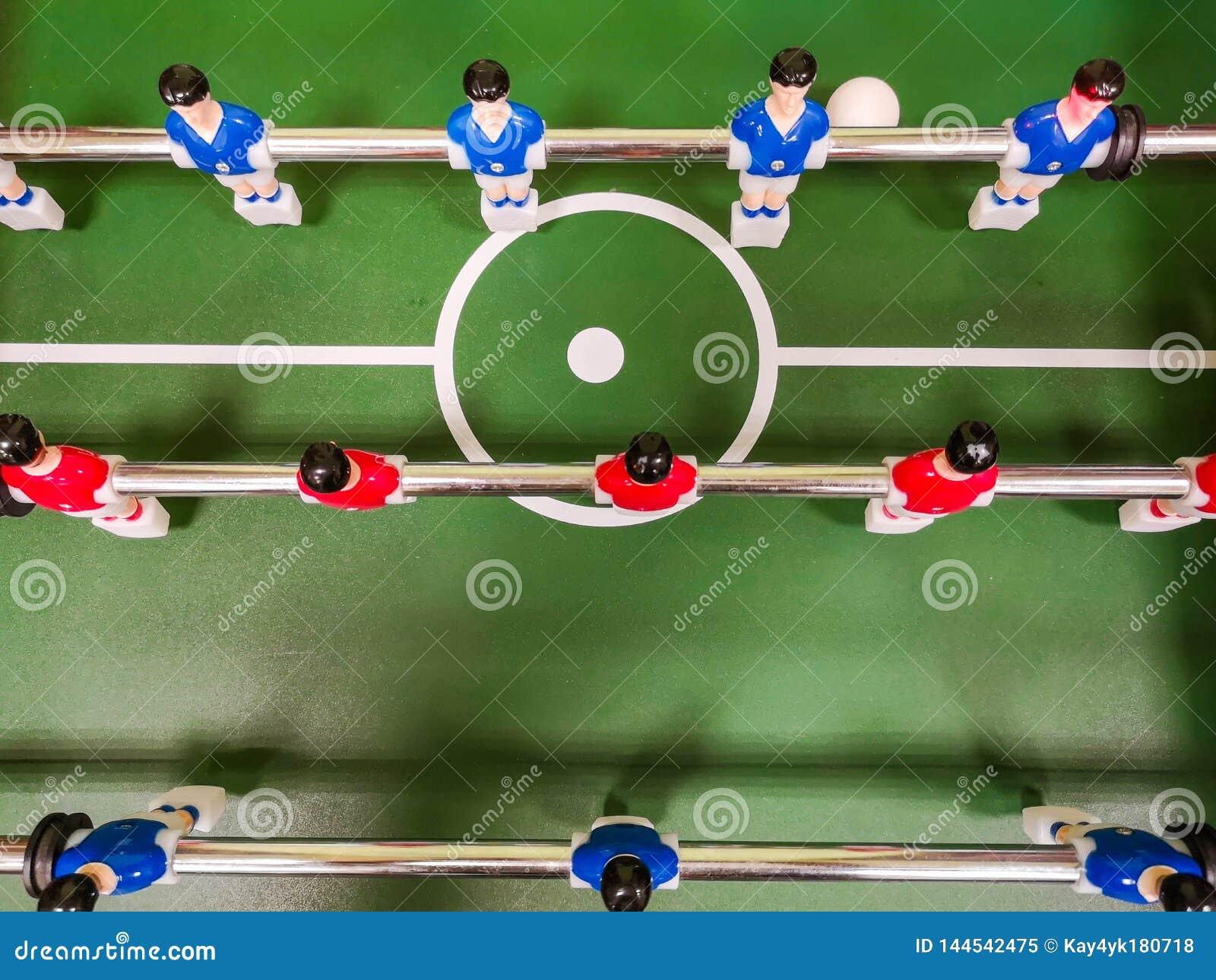 Друзья имея потеху совместно играя foosball Коллеги играя настольный футбол на перерыве Люди офиса наслаждаясь футбольным матчем