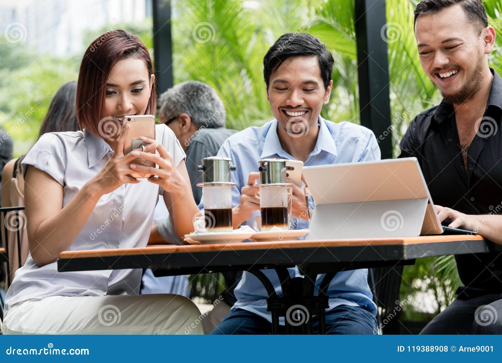 Друзья используя приборы соединились к беспроволочному интернету современной кофейни