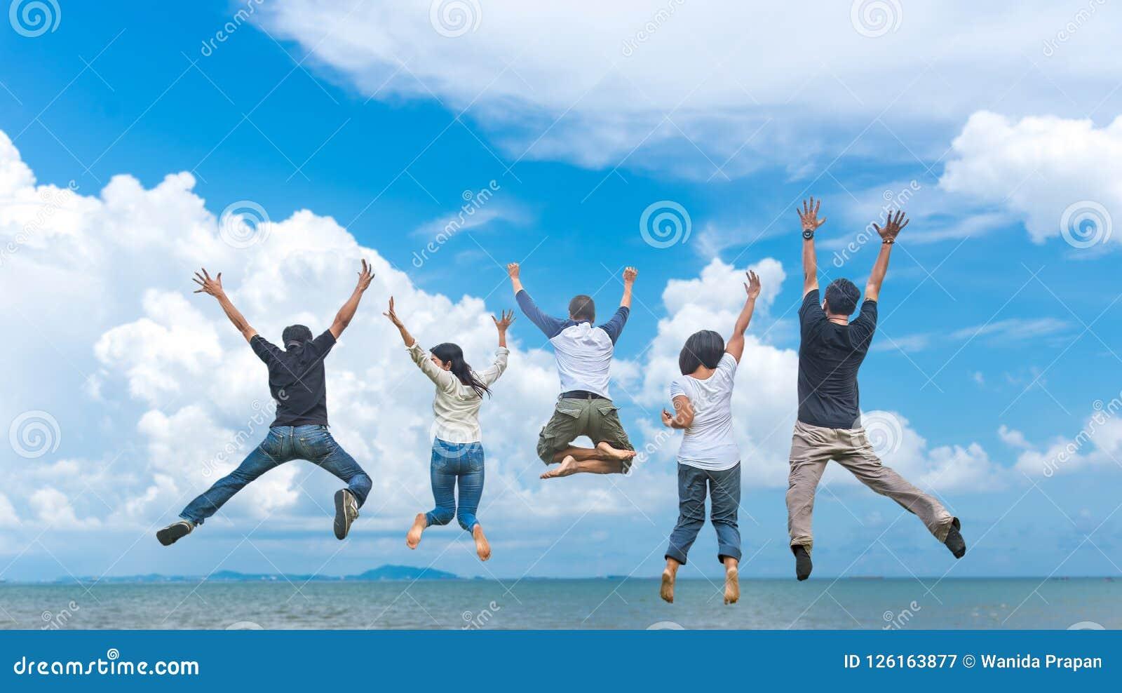 Друзья и сыгранность скача на пляж во время времени захода солнца для дела успеха