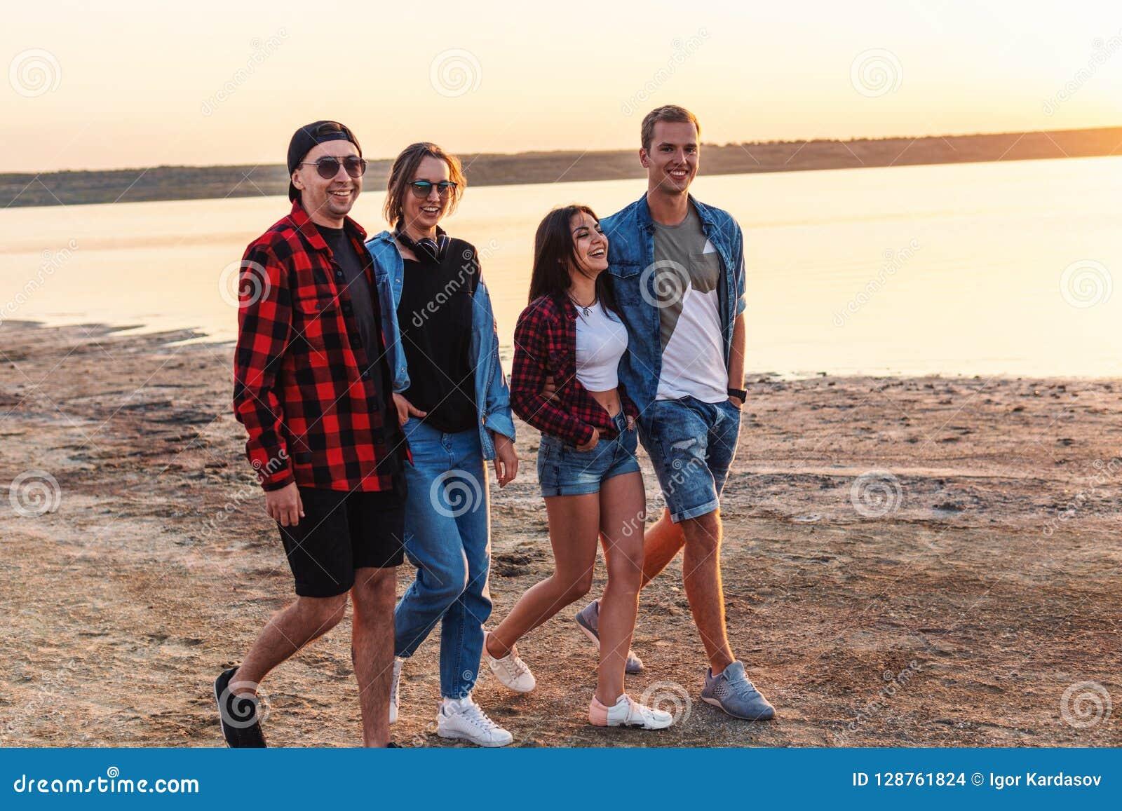Друзья на пляже совместно идя во время захода солнца
