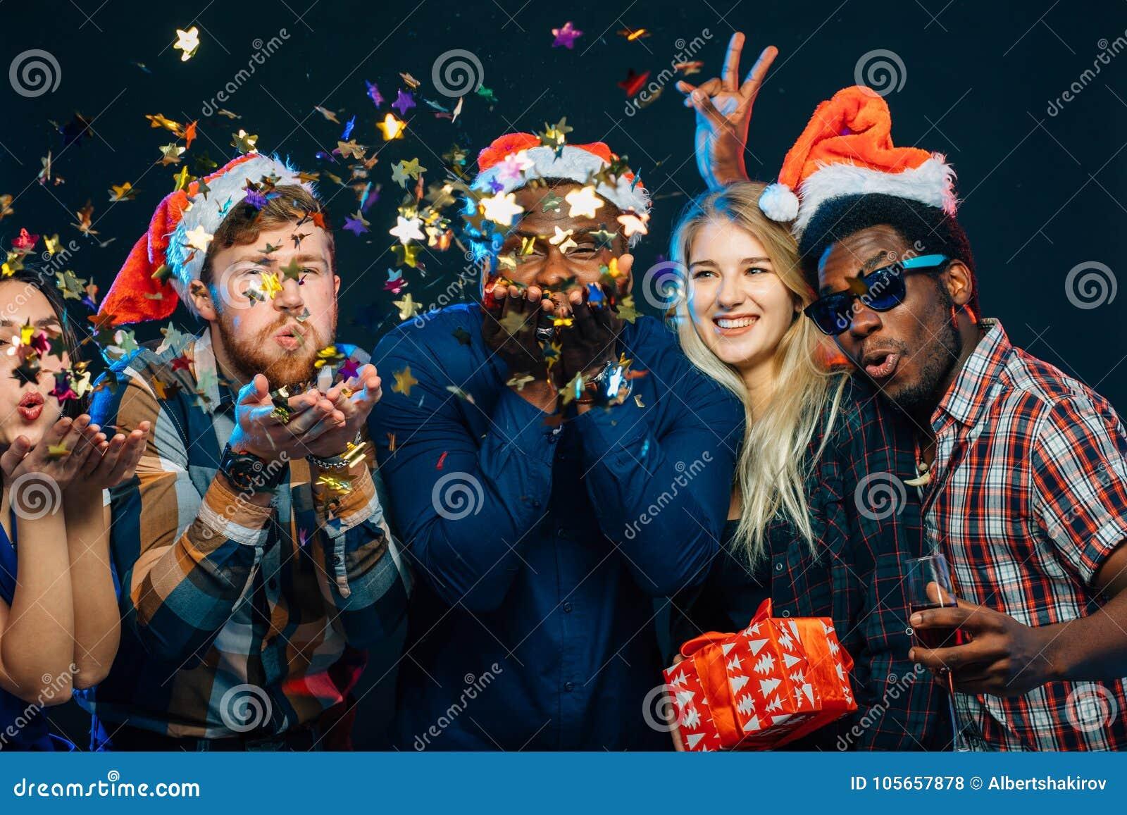 Друзья на ` s Нового Года party, носящ шляпы santa, танцы и дующ confetti
