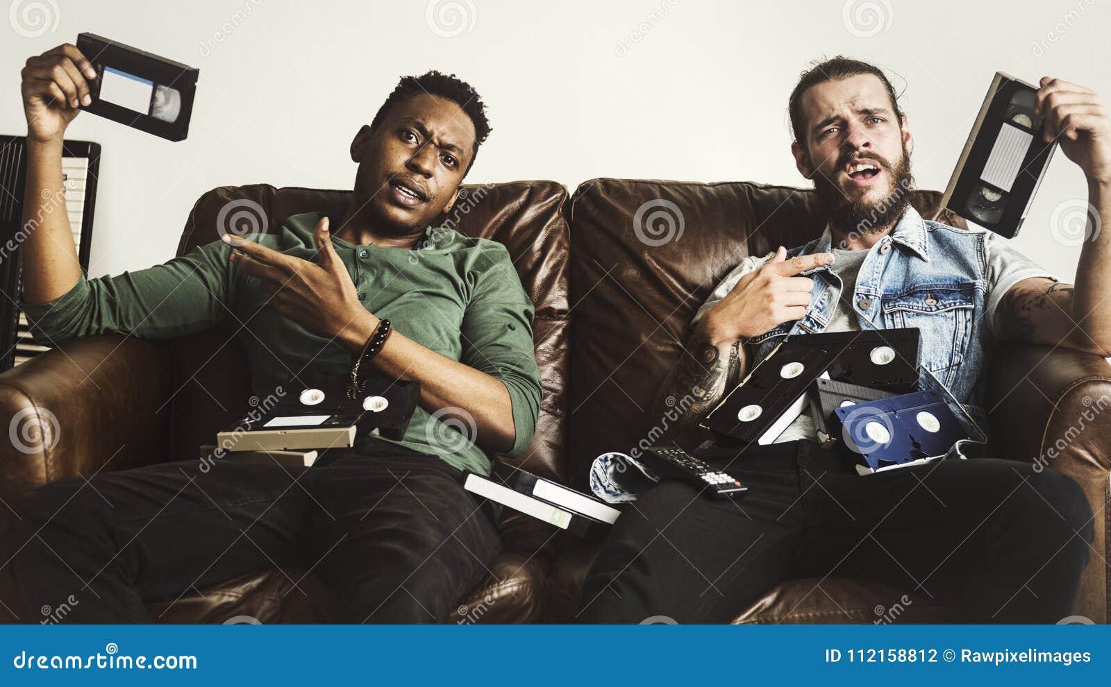 Друзья нося магнитные ленты для видеозаписи сидя на кресле