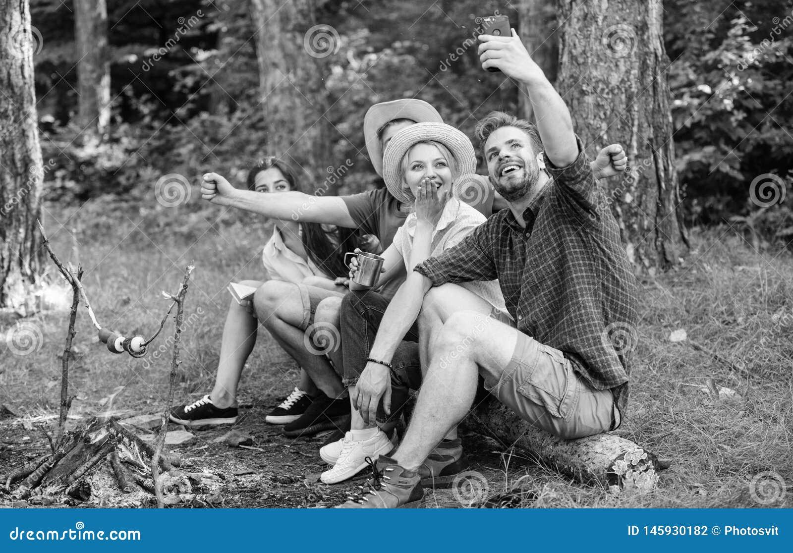 Друзья около костра наслаждаются каникулами и зажаренной в духовке едой Туристы сидят журнал около костра принимая смартфон фото