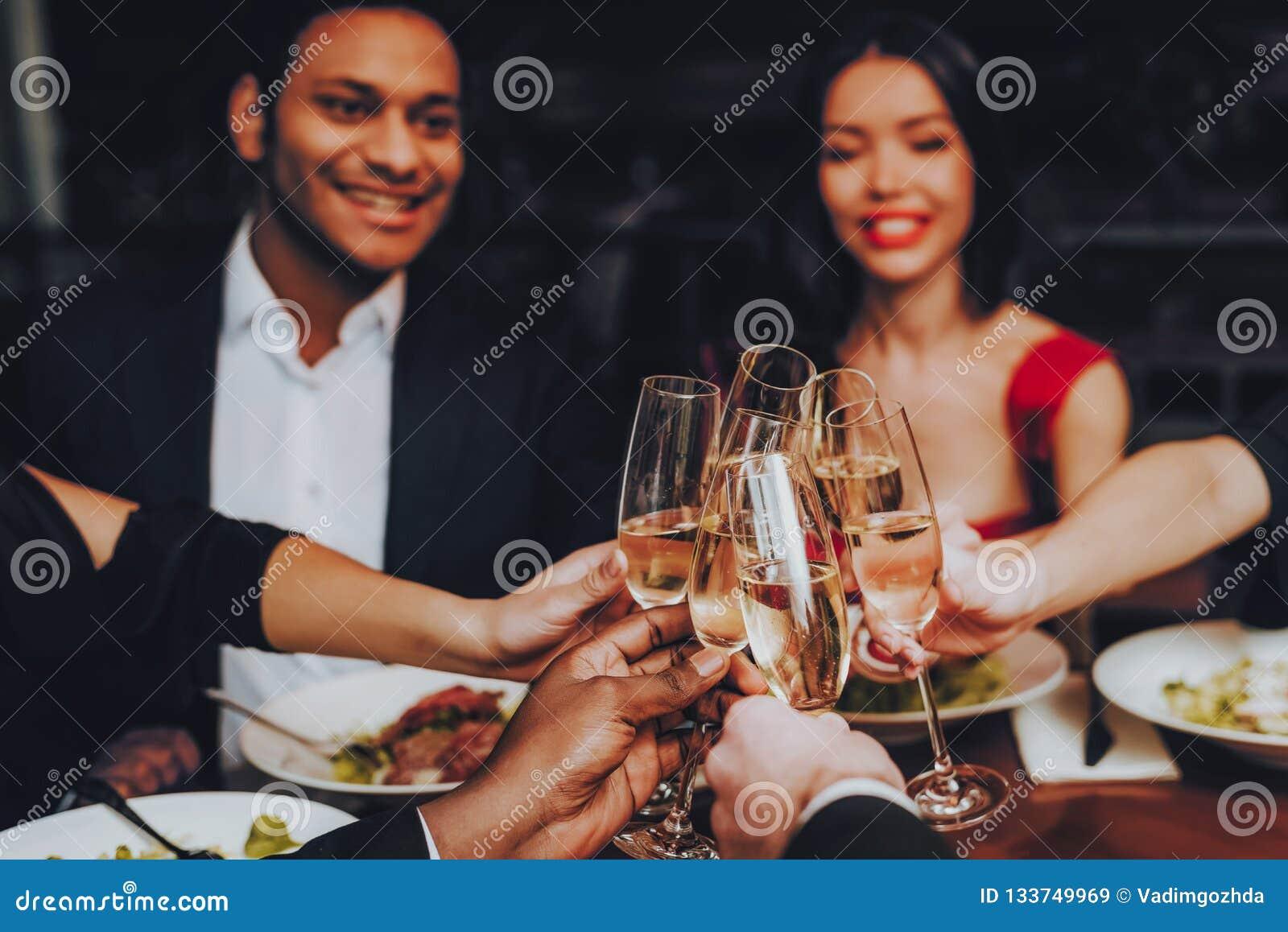 Друзья охлаждая вне наслаждаться едой в ресторане
