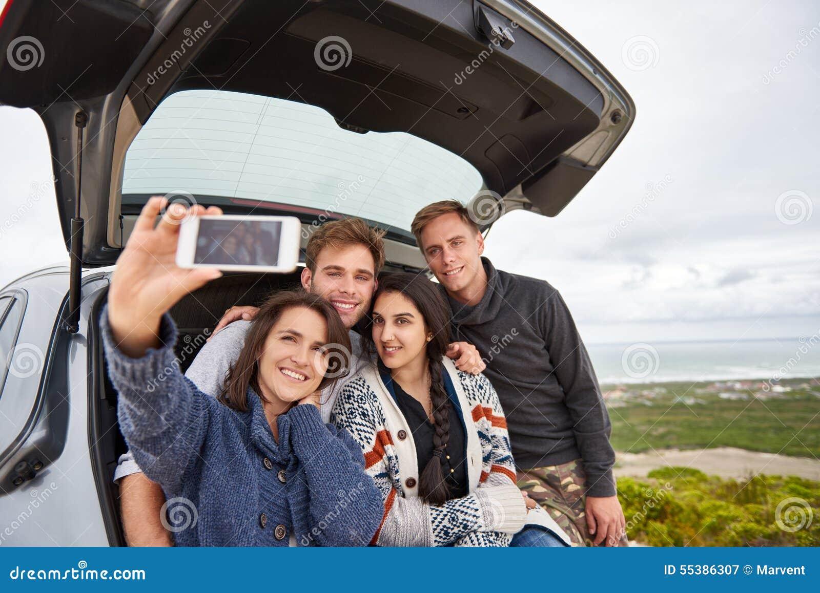 Друзья принимая selfie пока на roadtrip по побережью