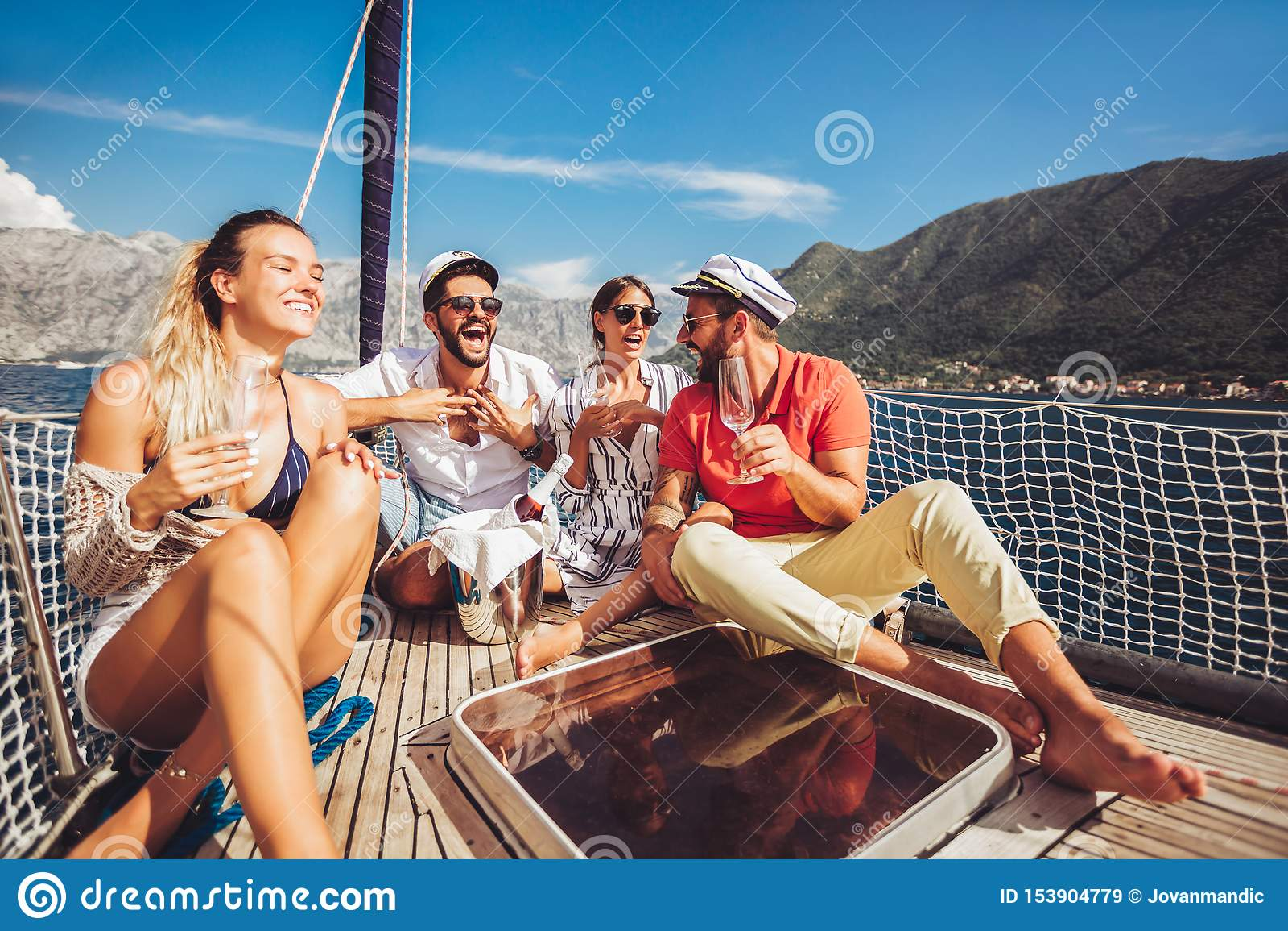 Друзья сидя на палубе парусника и имея потеху Каникулы, перемещение, море, приятельство и концепция людей